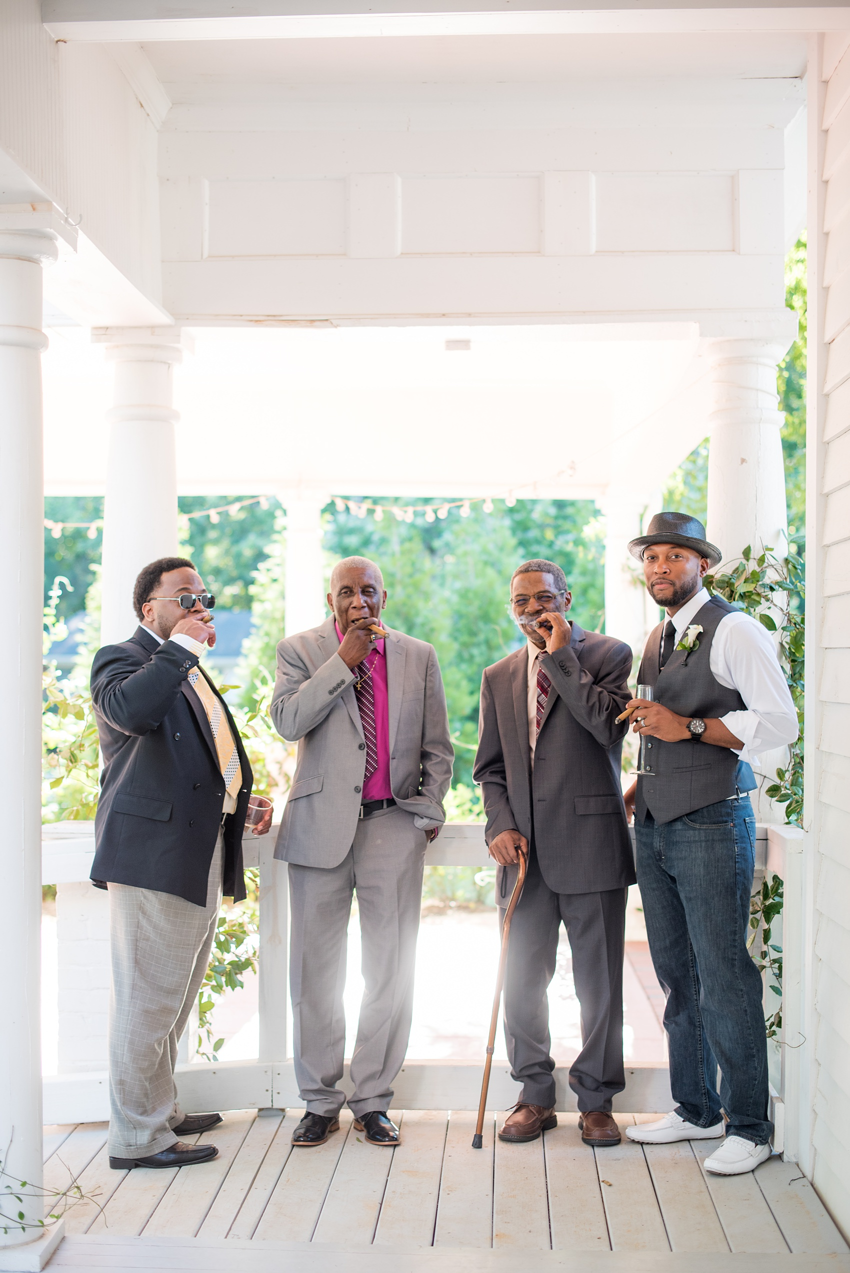 Mikkel Paige Photography pictures of a wedding at Leslie-Alford Mim's House in North Carolina for a Mad Dash Weddings event. Photo of the groom and men smoking cigars on the venue porch.
