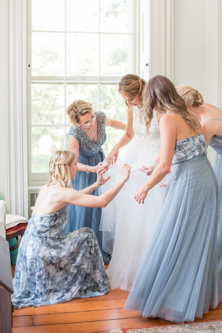 Mikkel Paige Photography photos from a Southwood Estate Wedding in Germantown, New York in the Hudson Valley. Picture of the bridesmaids helping the bride get ready in the historic home.