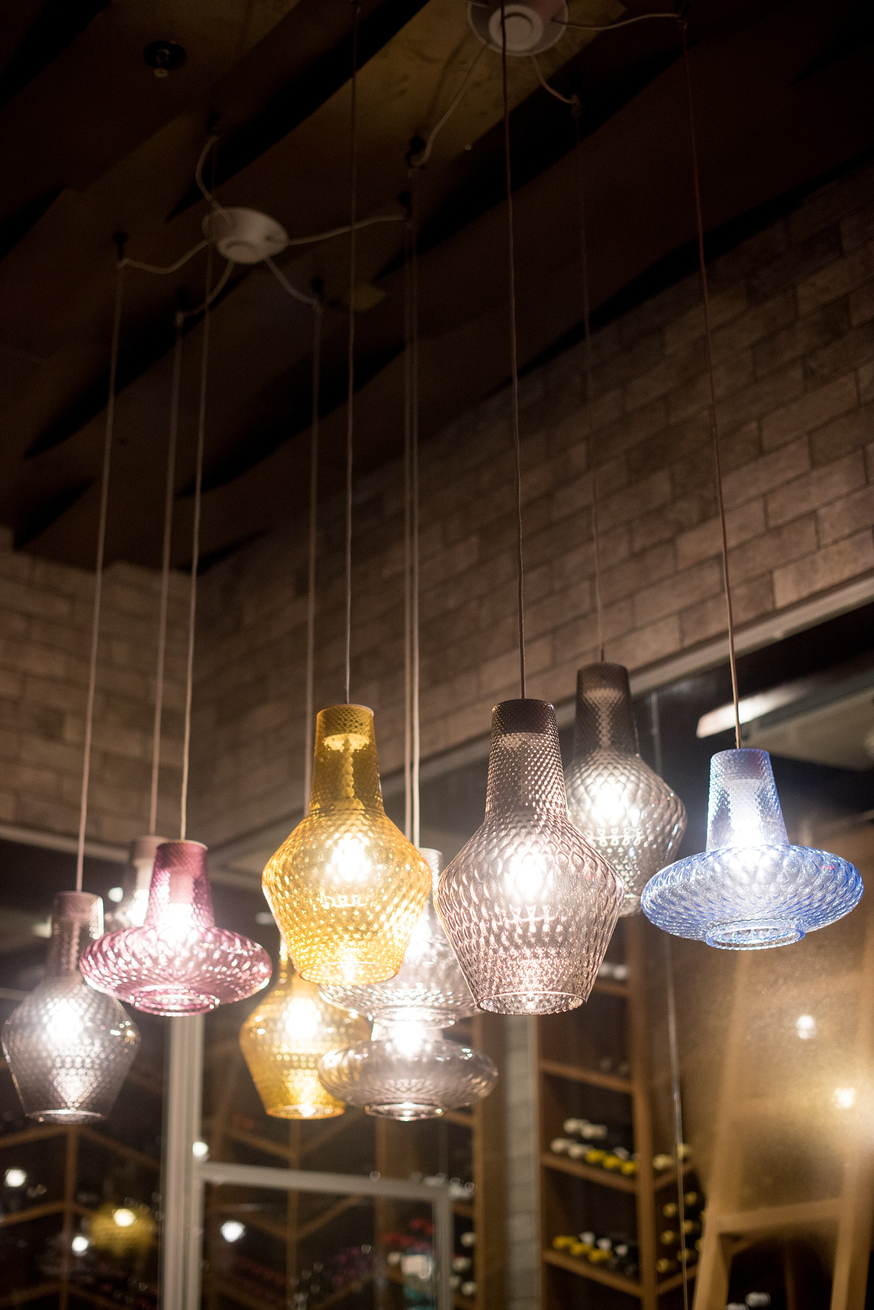 Photos of Vidrio restaurant in Raleigh, NC by Mikkel Paige Photography. Wedding venue in North Carolina with mediterranean and Spanish inspired art and interior design. Picture of different colored glass lamp hangings.