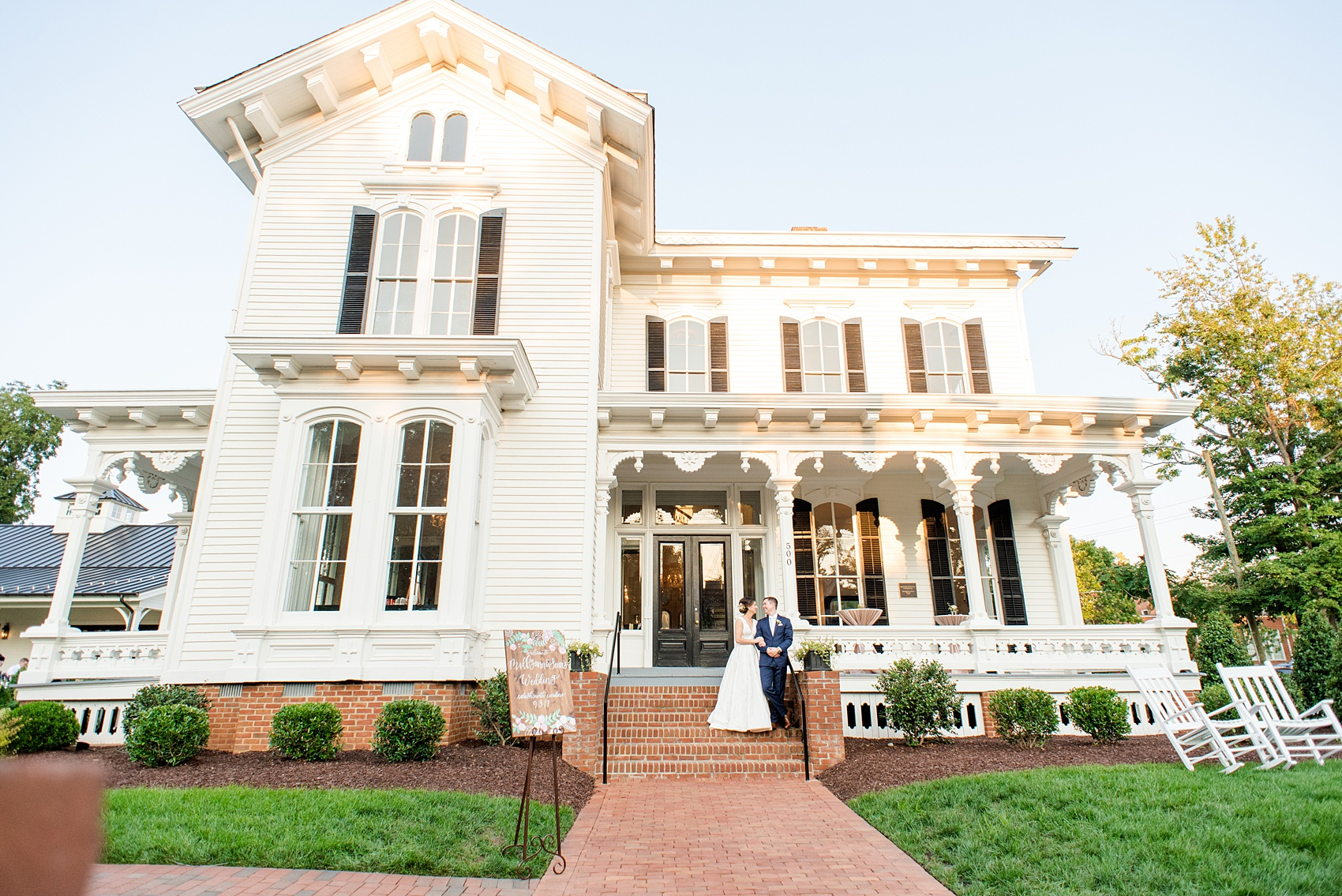 Mikkel Paige Photography pictures from a wedding at Merrimon-Wynne House in Raleigh, NC. Photo of the bride and groom in front if the historic home.