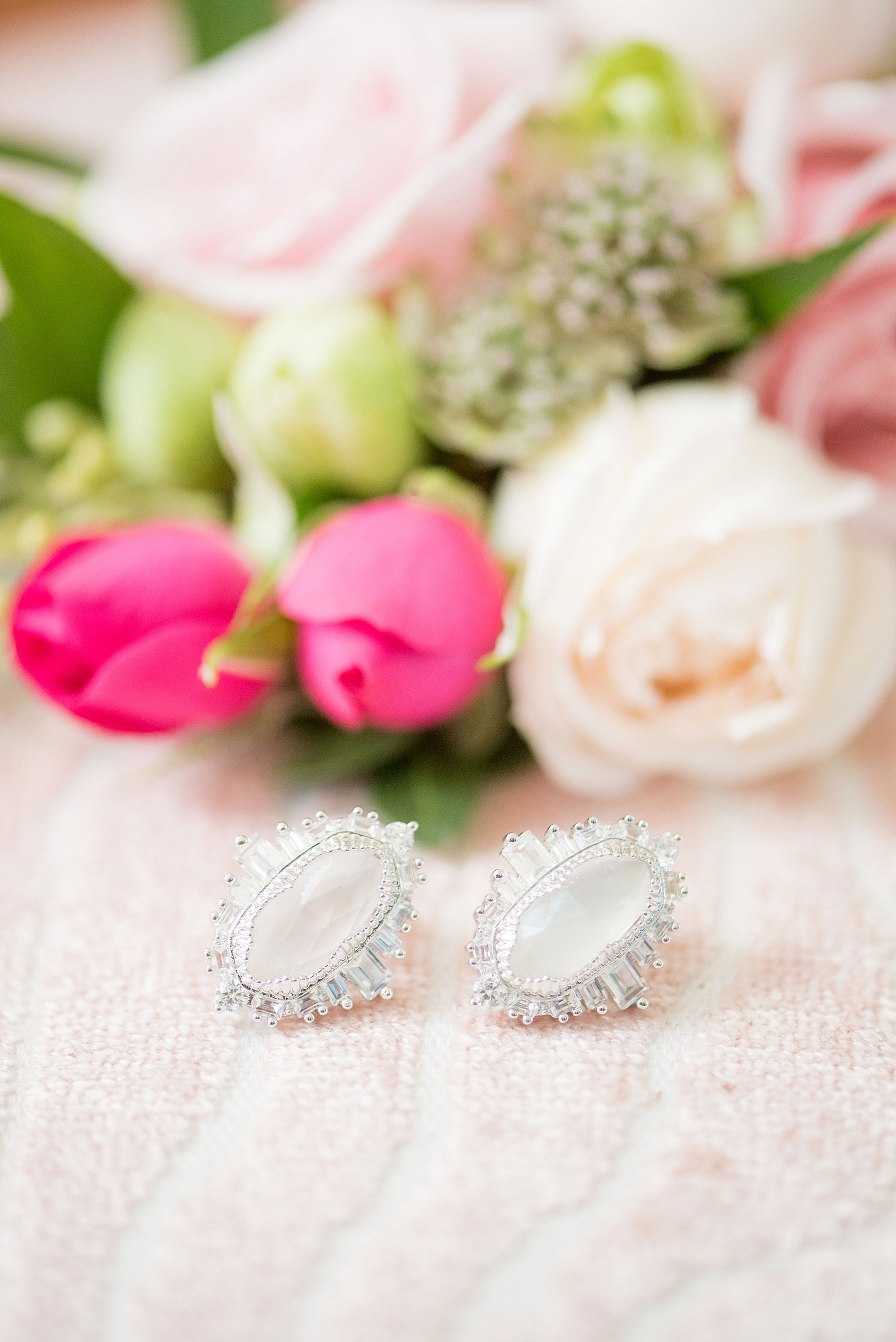 Mikkel Paige Photography pictures from a wedding at Merrimon-Wynne House in Raleigh, NC. Photo of the bride's white wedding earrings by Kendra Scott.