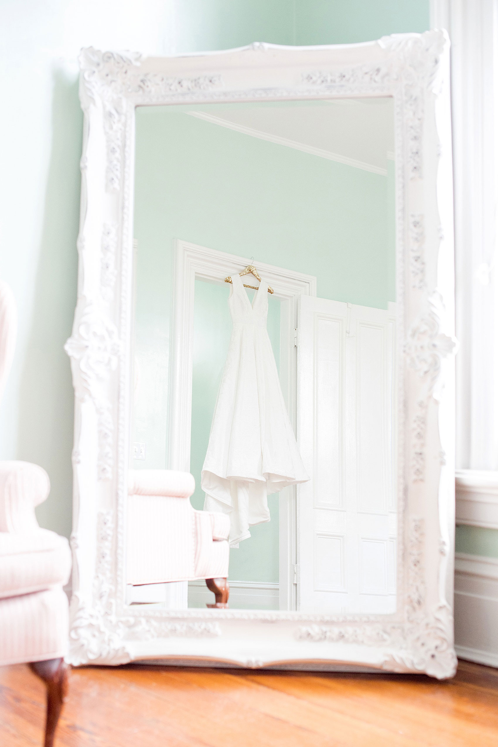 Mikkel Paige Photography pictures from a wedding at Merrimon-Wynne House in Raleigh, NC. Photo of the bride's Kate McDonald dress reflecting in a mirror in the bridal suite.