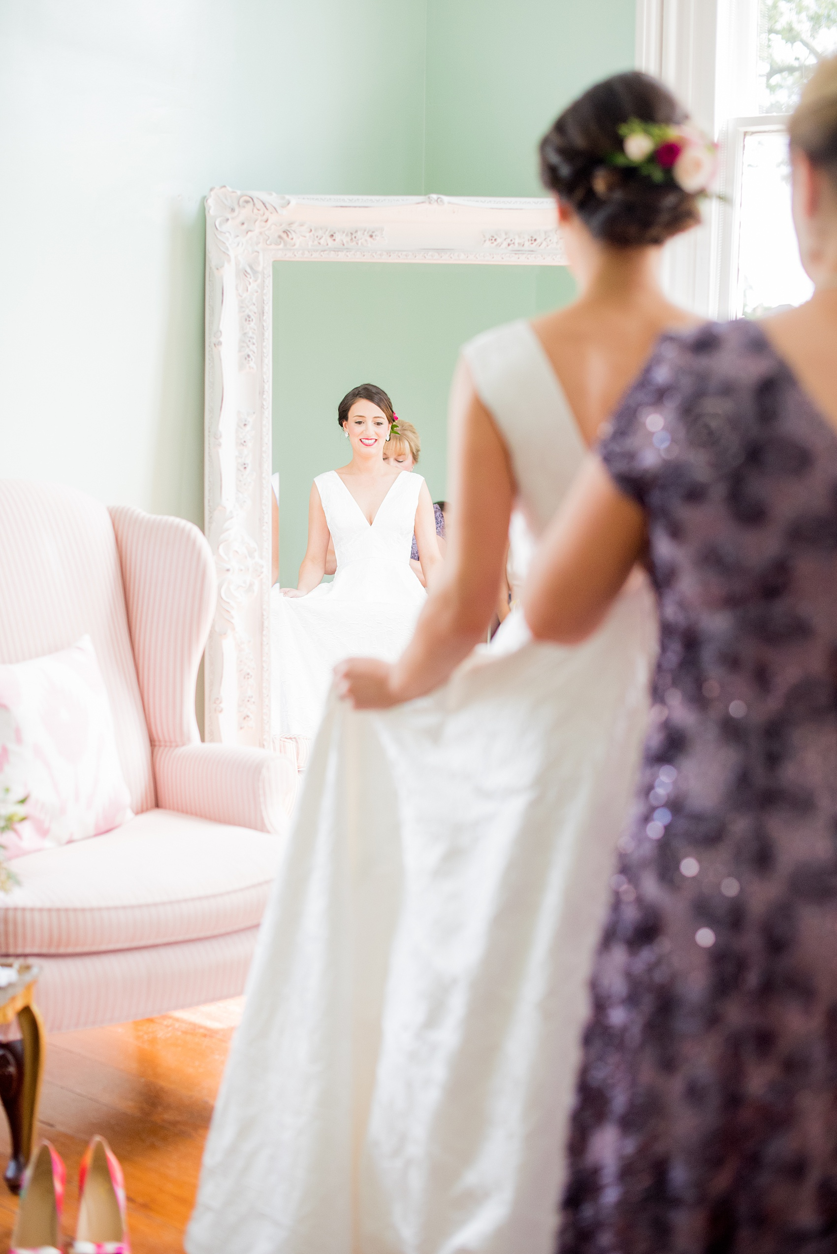 Mikkel Paige Photography pictures from a wedding at Merrimon-Wynne House in Raleigh, NC. Photo of the bride reflecting in a mirror in the bridal suite as her mother helps her get ready.