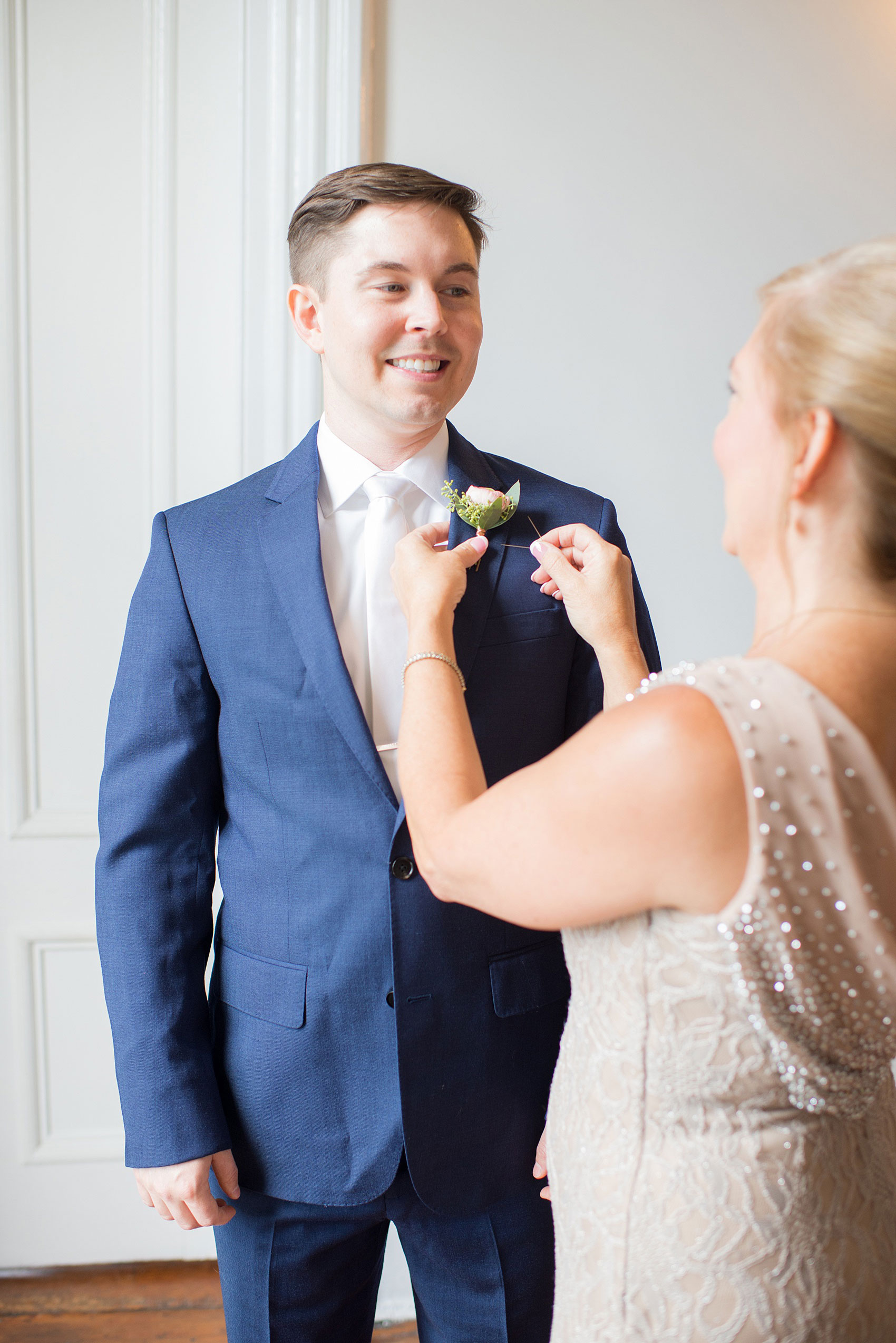 Mikkel Paige Photography pictures from a wedding at Merrimon-Wynne House in Raleigh, NC. Photo of the groom's mother pinning on his boutonniere.