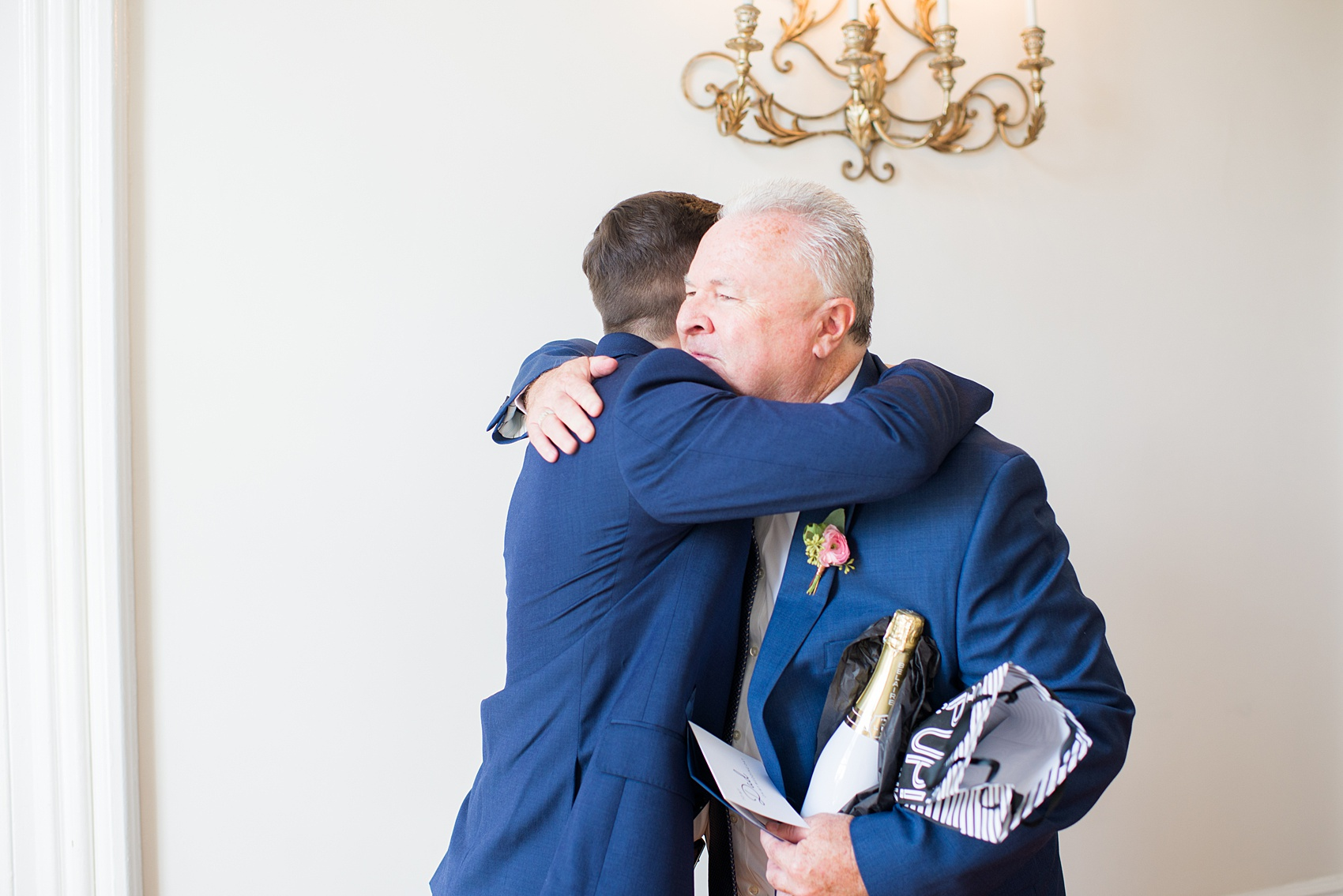 Mikkel Paige Photography pictures from a wedding at Merrimon-Wynne House in Raleigh, NC. Photo of the groom hugging his father.