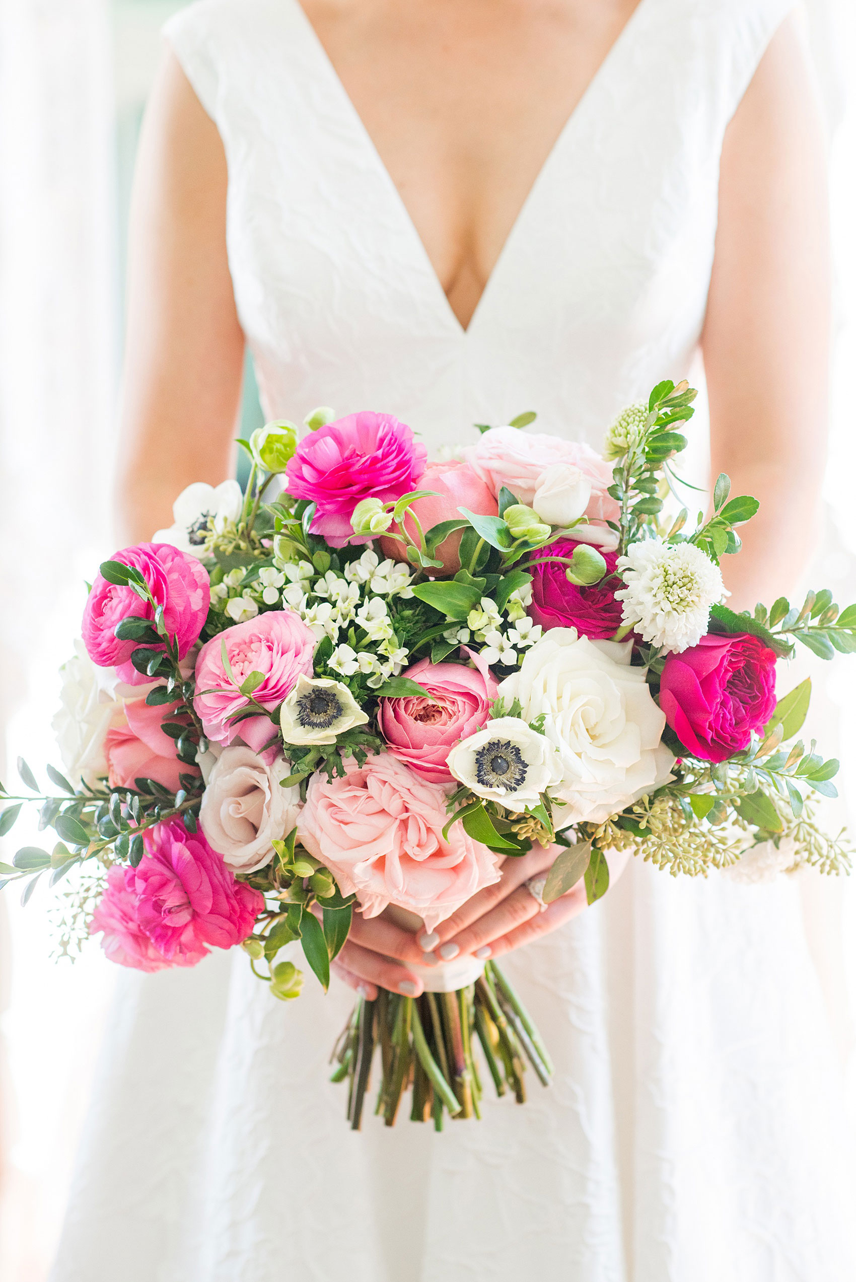 Mikkel Paige Photography pictures from a wedding at Merrimon-Wynne House in Raleigh, NC. Photo of the bride's colorful bouquet with light and hot pinks, white and greens created by Eclectic Sage.