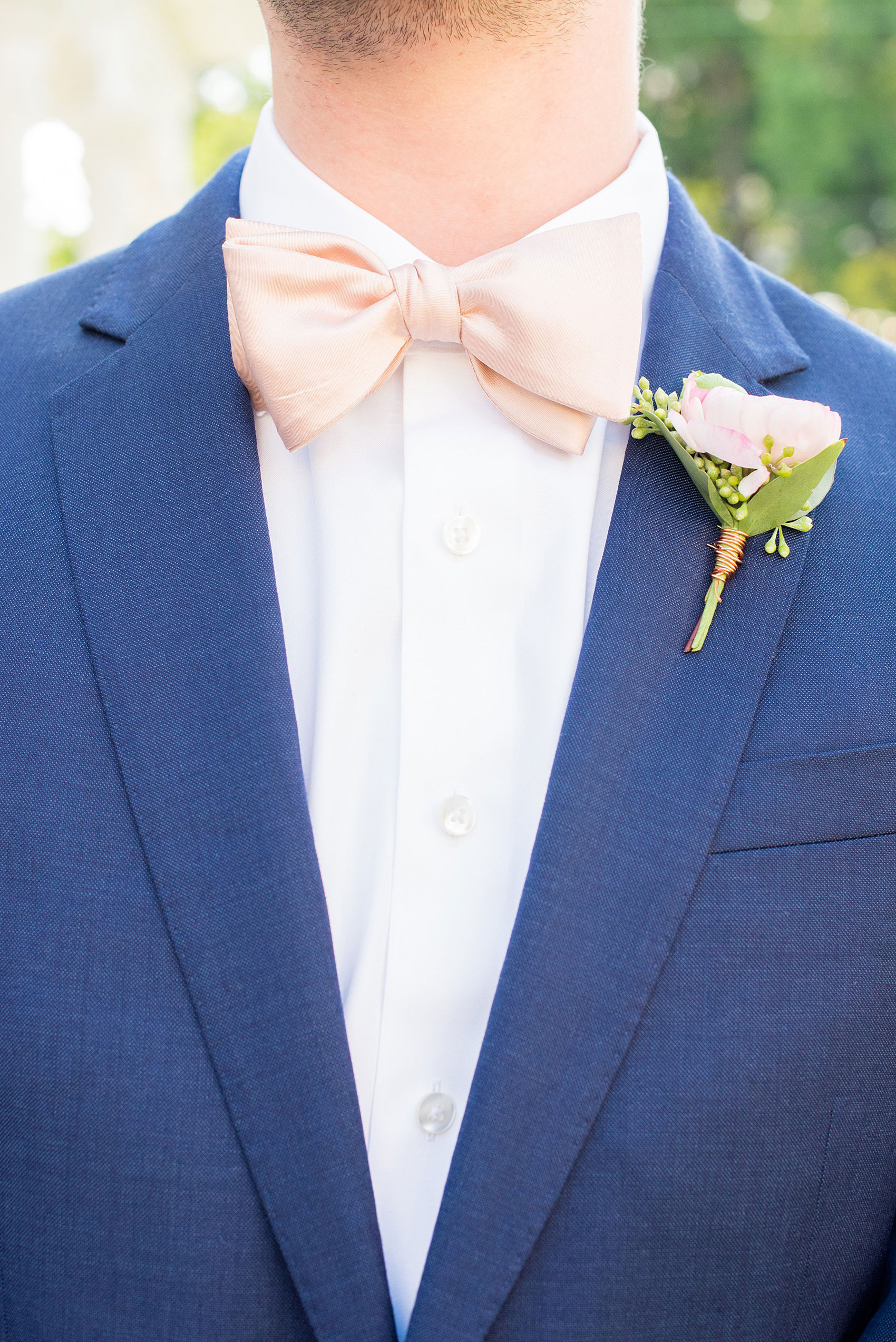 Mikkel Paige Photography pictures from a wedding at Merrimon-Wynne House in Raleigh, NC. Detail photo of the groomsman's blue linen suit, pink boutonniere tied with copper wire and pink bow tie.