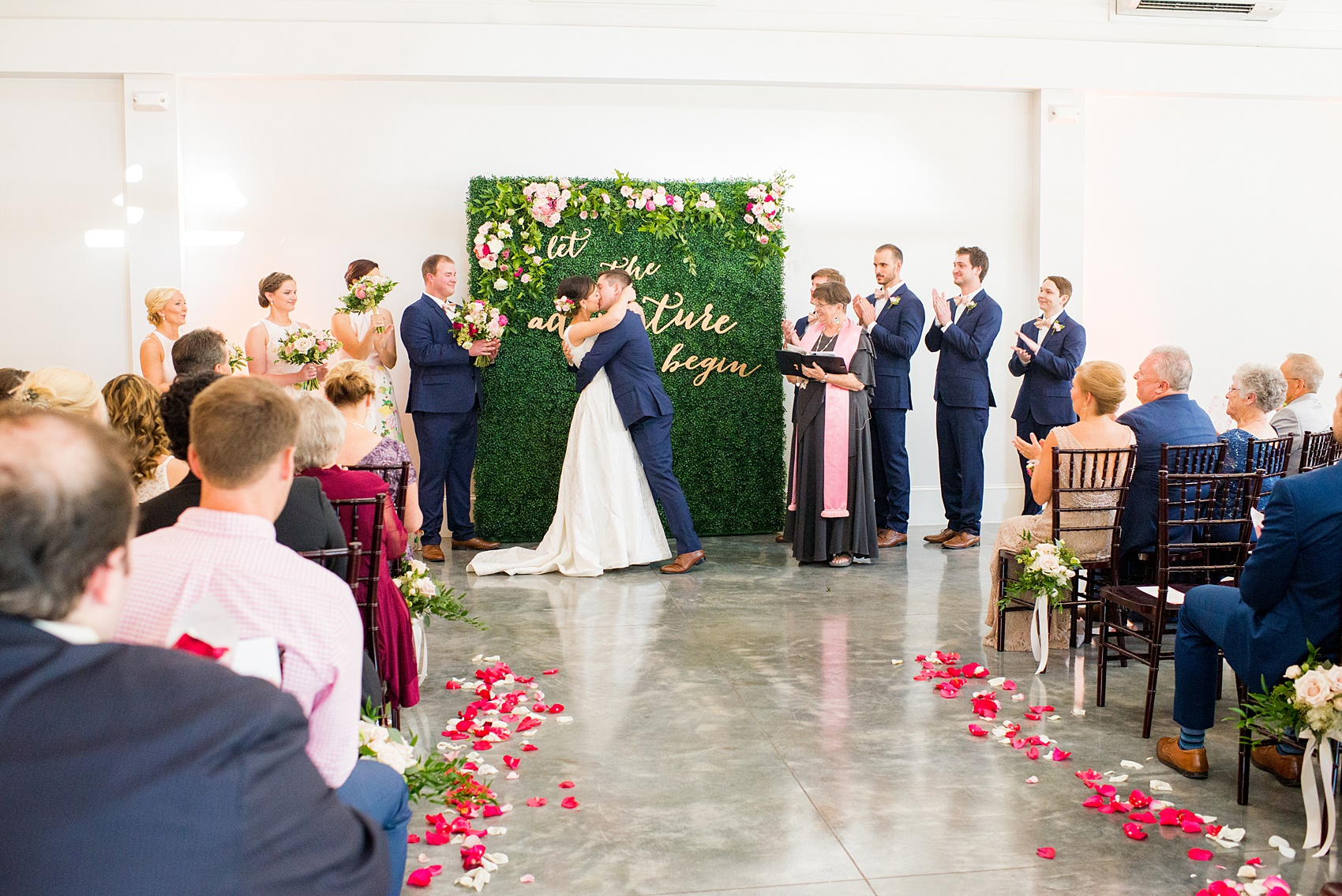 Mikkel Paige Photography pictures from a wedding at Merrimon-Wynne House in Raleigh, NC. Photo of the bride and groom's first kiss after their ceremony with a greenery backdrop.