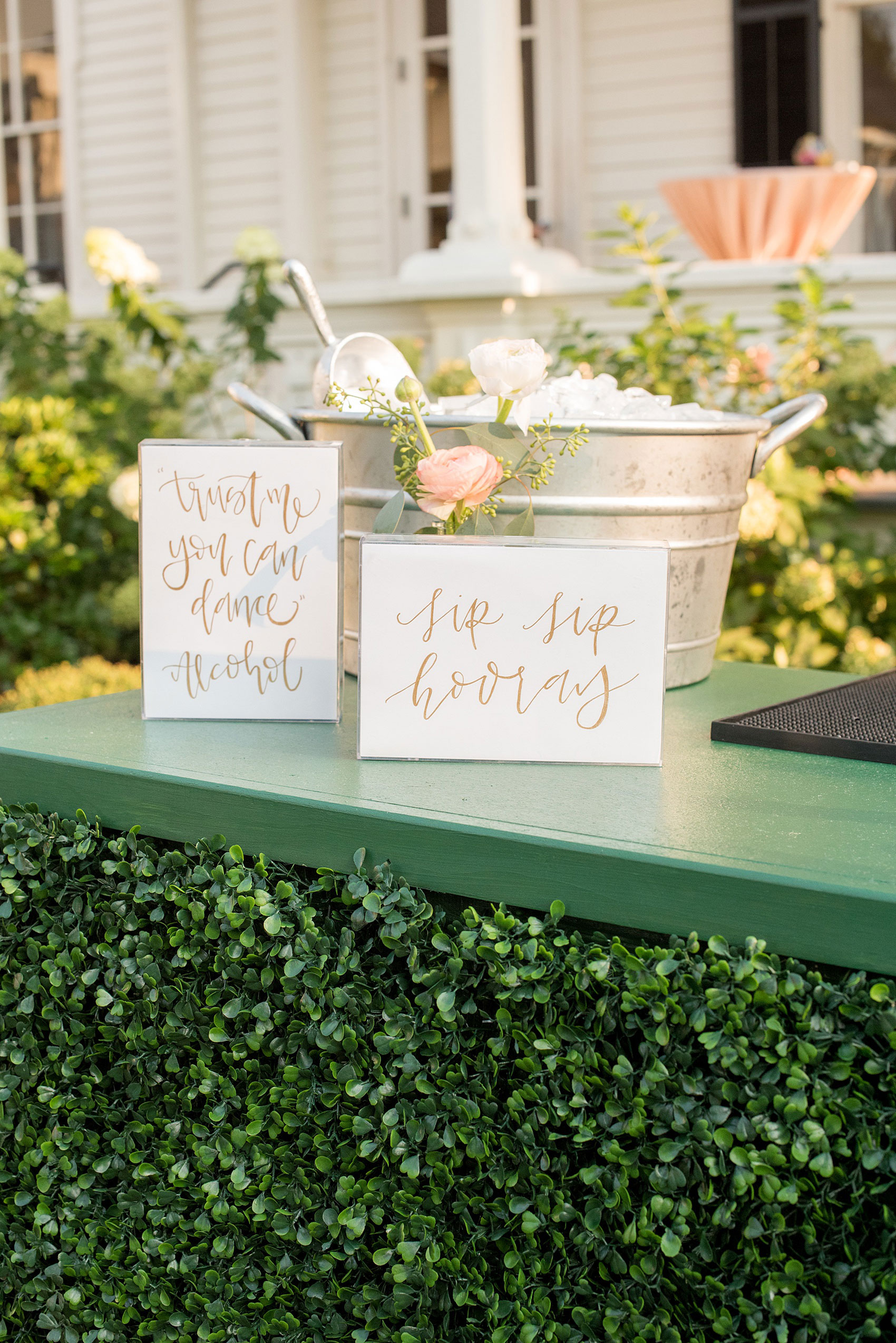 Mikkel Paige Photography pictures from a wedding at Merrimon-Wynne House in Raleigh, NC. Photo of the boxwood bar with script signage.