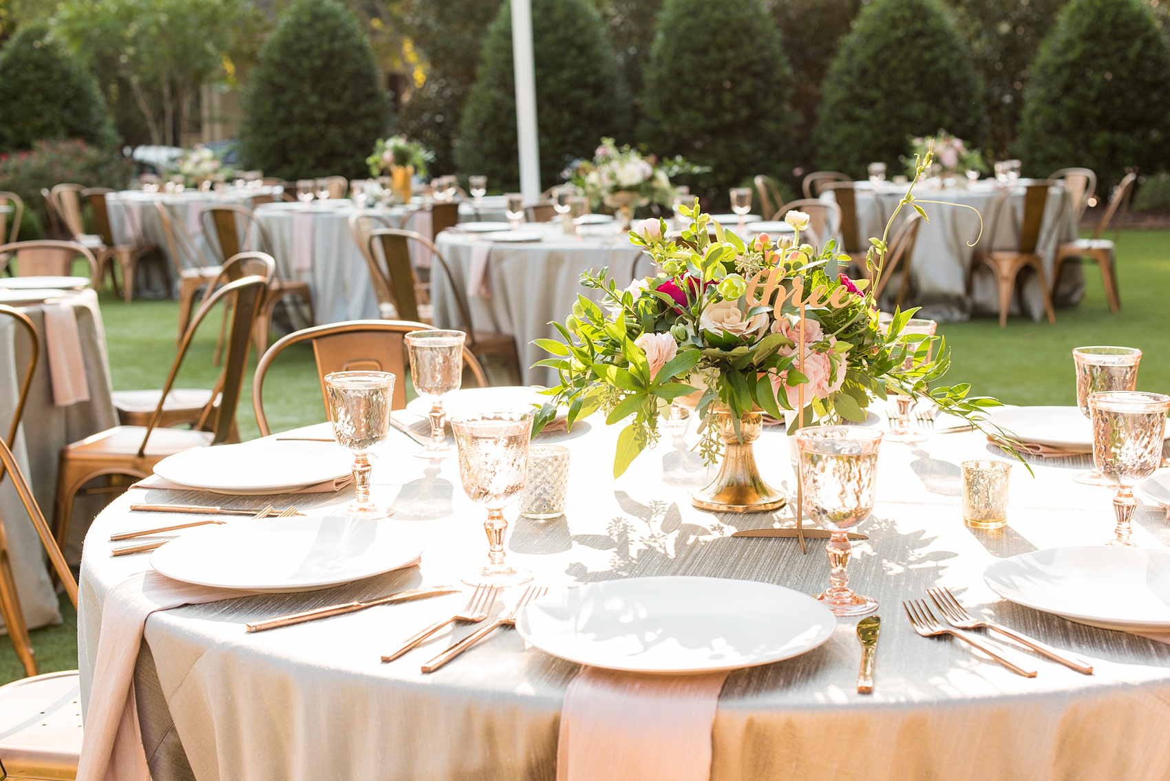 Mikkel Paige Photography pictures from a wedding at Merrimon-Wynne House in Raleigh, NC. Photo of the table centerpieces with geometric glass candle holders, script gold numbers, copper flatware, and pink glasses.