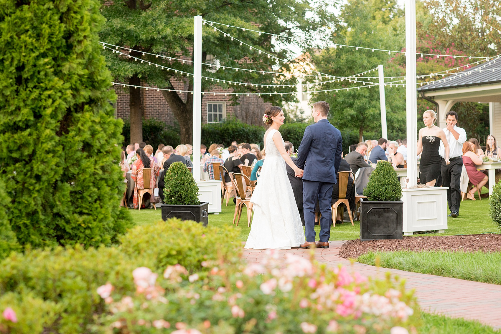 Mikkel Paige Photography pictures from a wedding at Merrimon-Wynne House in Raleigh, NC. Photo of the bride and groom joining their outdoor reception dinner.