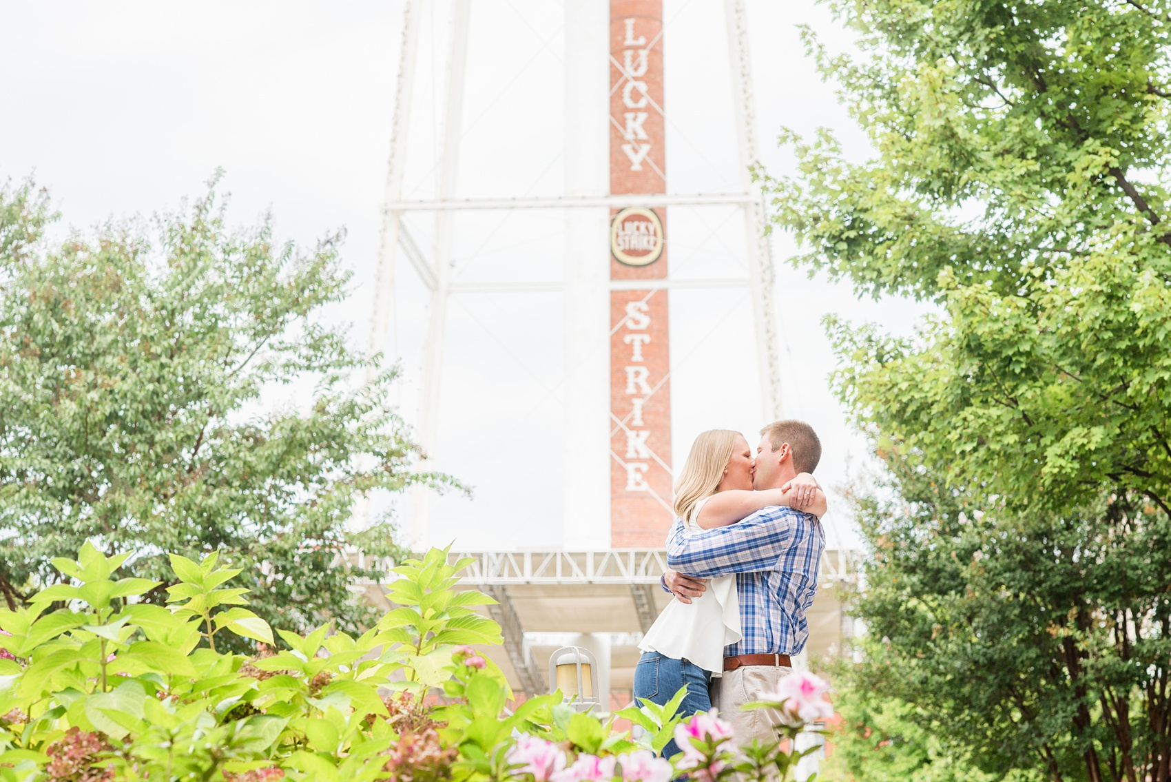 """Mikkel Paige Photography photos from an engagement session at Durham's American Tobacco Campus in North Carolina. Picture of the couple with a """"Lucky Strike"""" stack."""