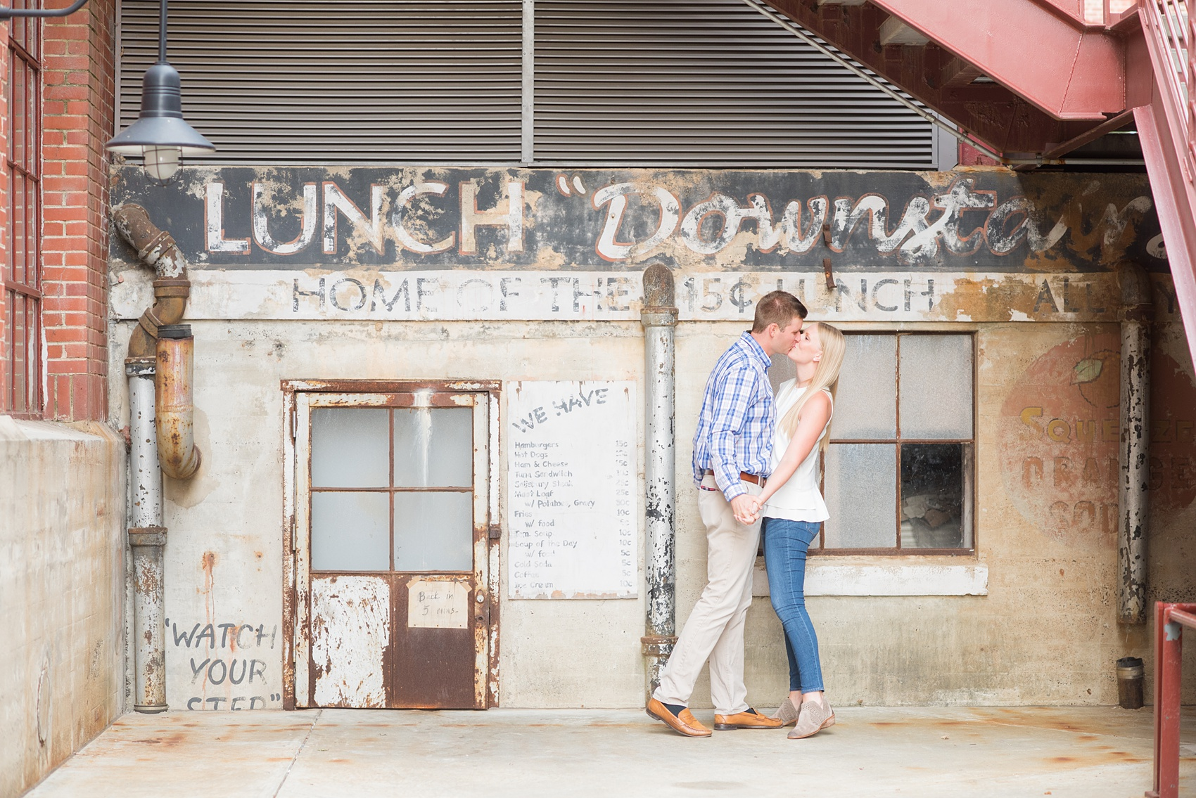 Mikkel Paige Photography photos from an engagement session at Durham's American Tobacco Campus in North Carolina. Picture of the couple near vintage signage.