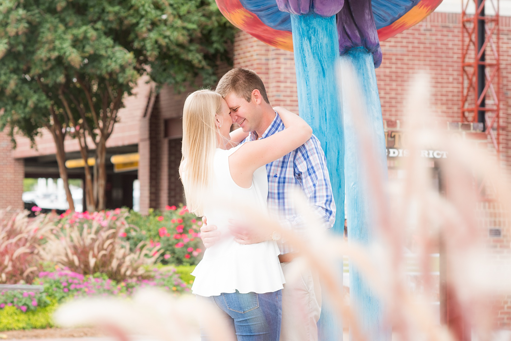 Mikkel Paige Photography photos from an engagement session at Durham's American Tobacco Campus in North Carolina. Colorful picture with the couple embracing.