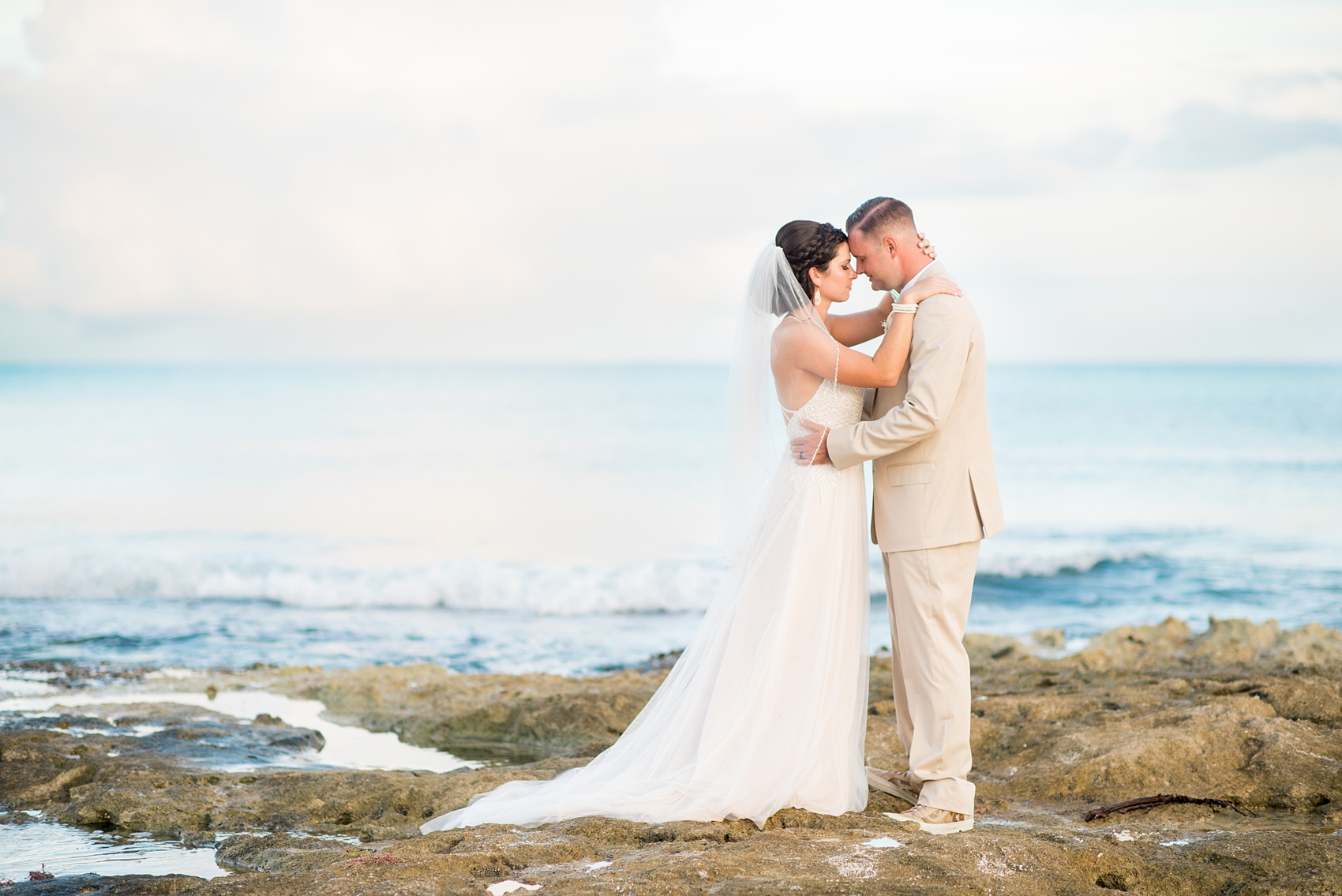 Mikkel Paige Photography photos from a wedding at Grand Paraiso, Mexico, Playa del Carmen Iberostar resort. Picture of the bride and groom on the ocean.
