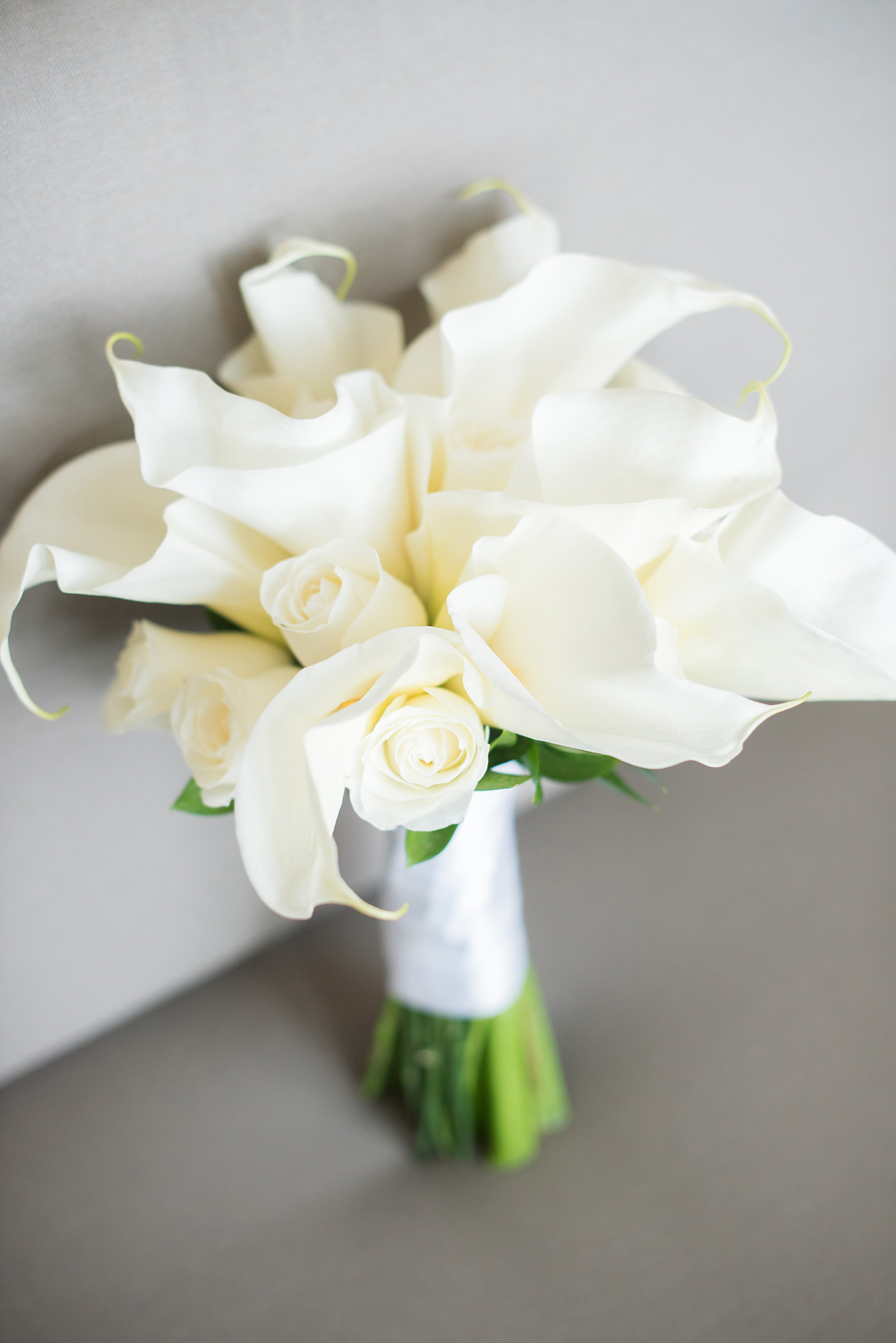 Mikkel Paige Photography photos from a wedding at Grand Paraiso, Mexico, Playa del Carmen Iberostar resort. Picture of the bride's calla lily and rose white bouquet.
