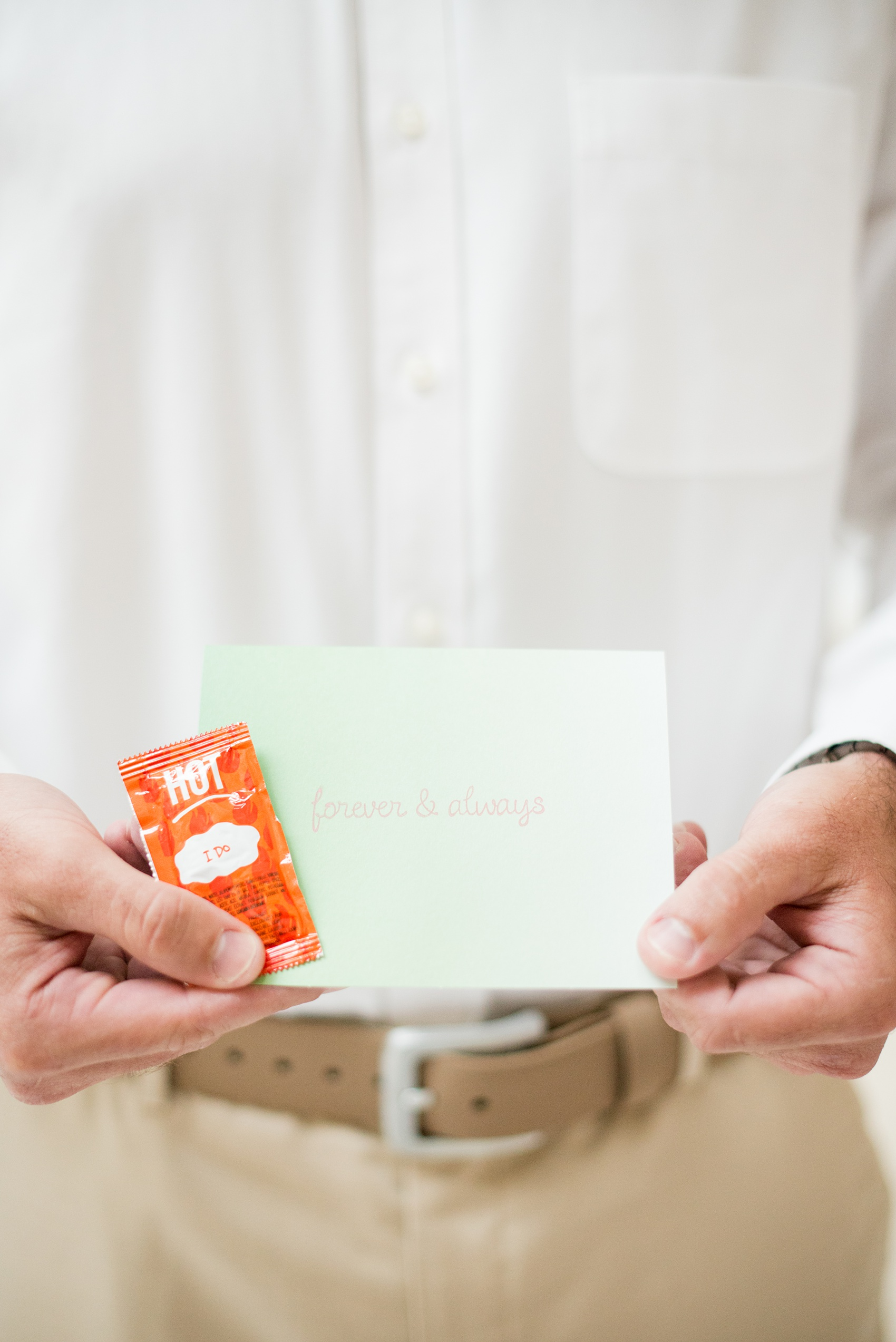 """Mikkel Paige Photography photos from a wedding at Grand Paraiso, Mexico, Playa del Carmen Iberostar resort. Picture of the groom reading a letter form his bride and an """"I Do"""" hot sauce packet."""