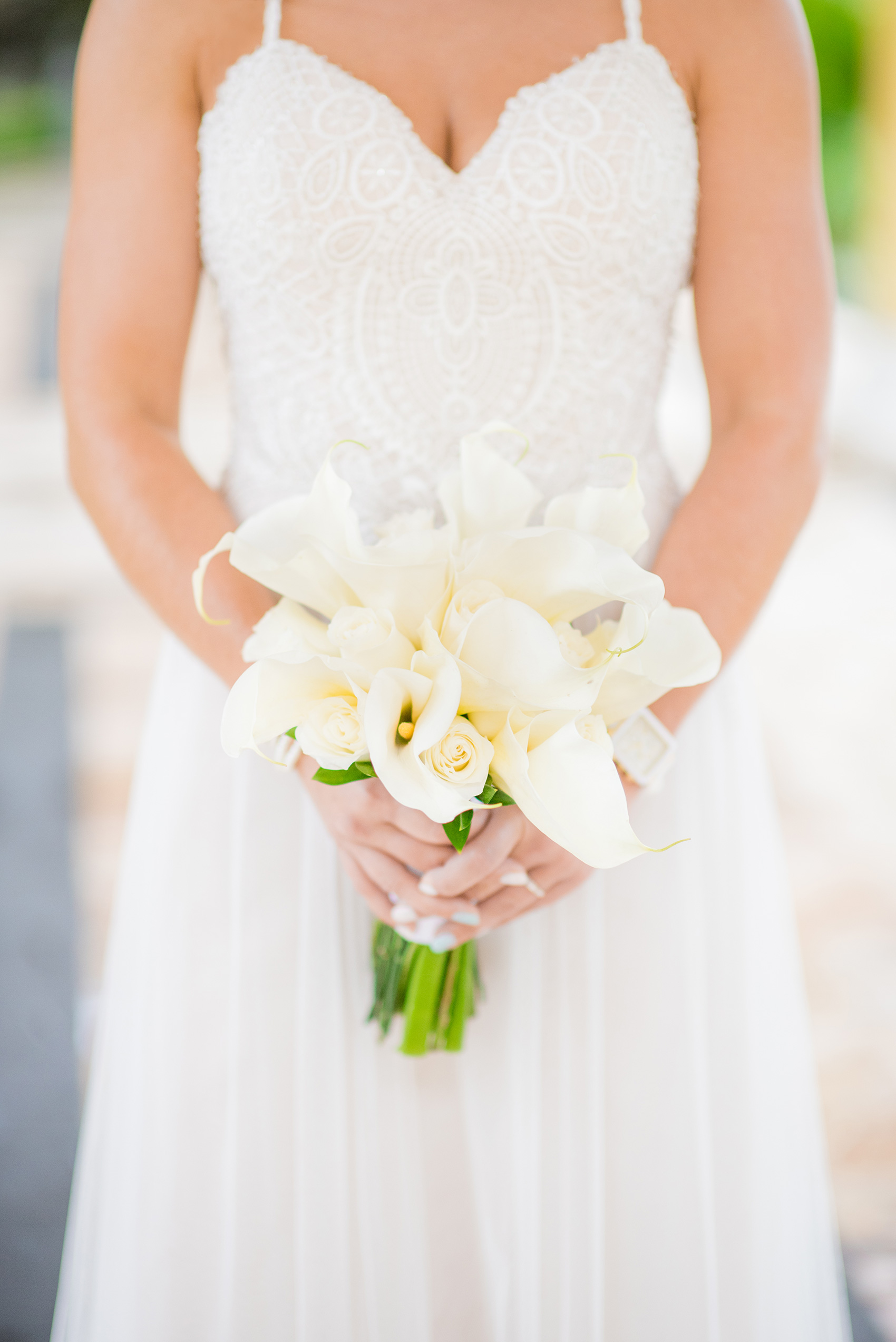 Mikkel Paige Photography photos from a wedding at Grand Paraiso, Mexico, Playa del Carmen Iberostar resort. Picture of the bride holding her calla lily and rose white bouquet.