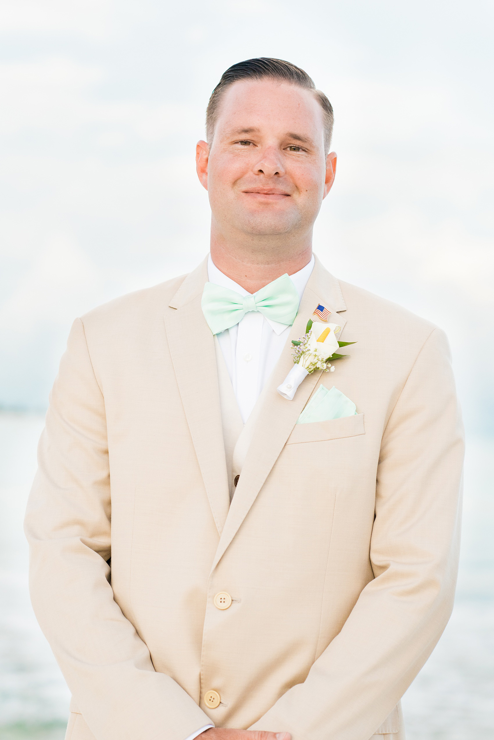 Mikkel Paige Photography photos from a wedding at Grand Paraiso, Mexico, Playa del Carmen Iberostar resort. Picture of the groom in a tan suit and light mint green bow tie.