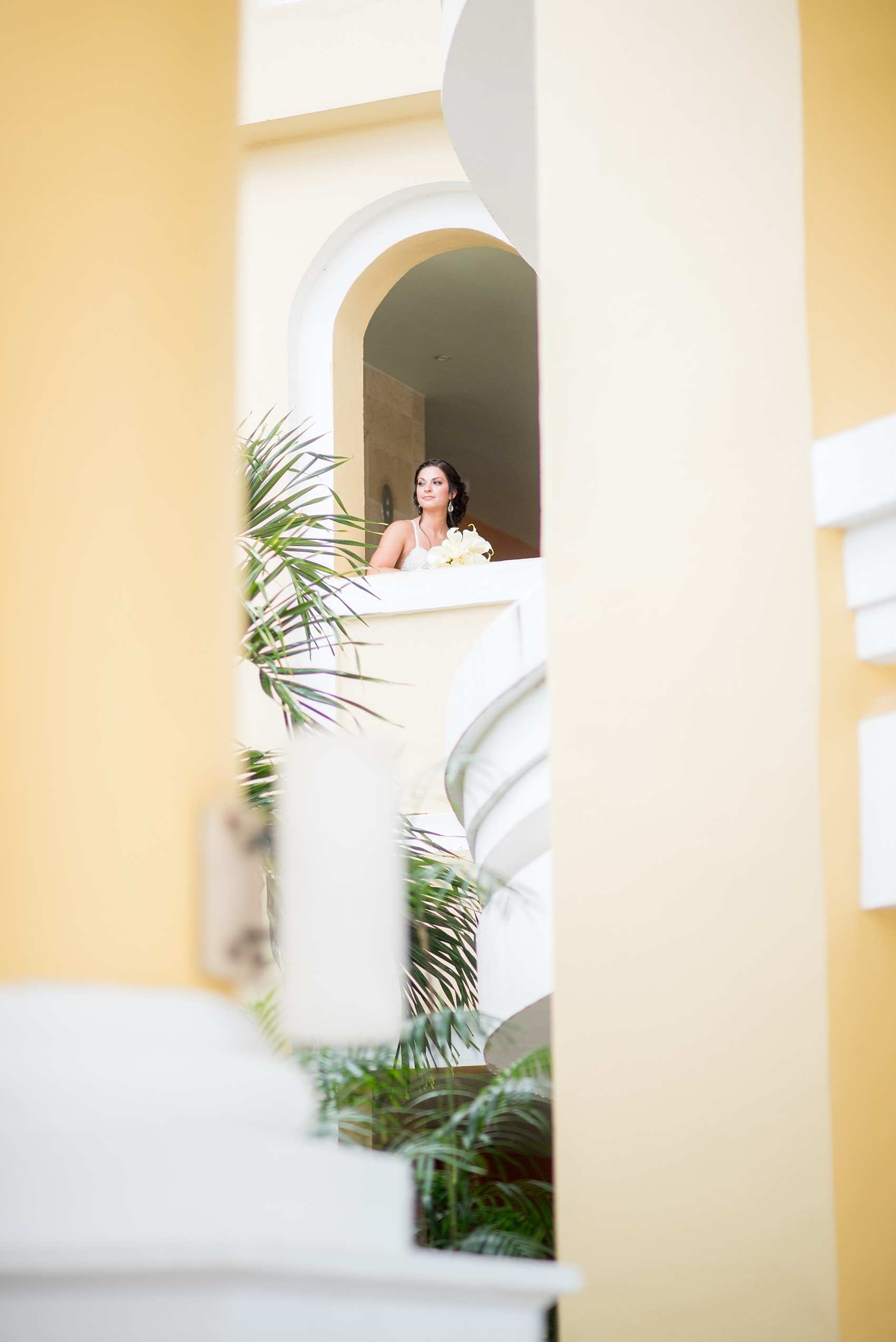 Mikkel Paige Photography photos from a wedding at Grand Paraiso, Mexico, Playa del Carmen Iberostar resort. Picture of the bride in a window frame staircase.