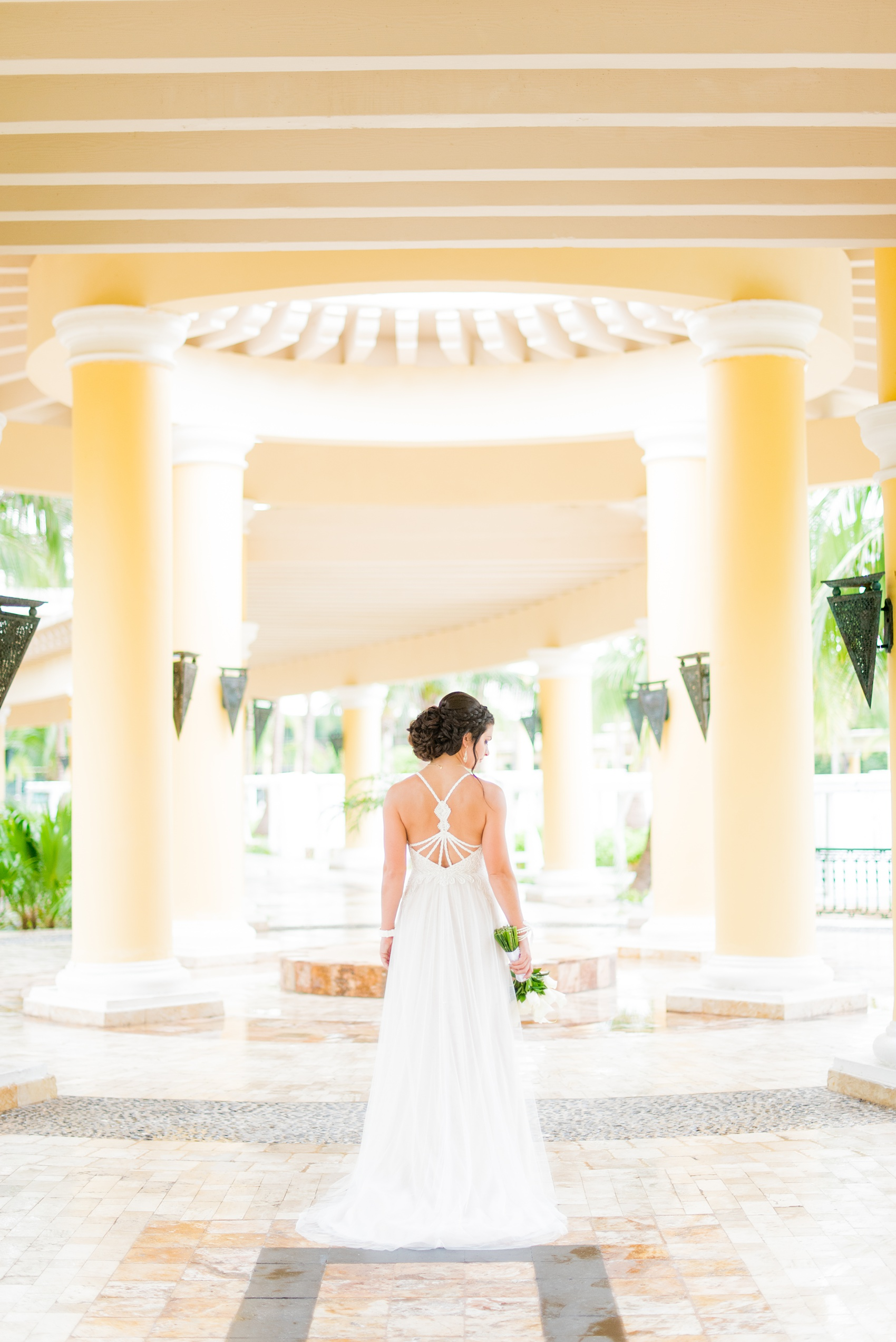 Mikkel Paige Photography photos from a wedding at Grand Paraiso, Mexico, Playa del Carmen Iberostar resort. Picture of the back of the bride's beach dress with string detail.