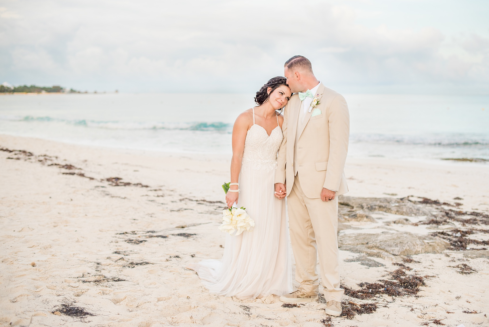 Mikkel Paige Photography photos from a wedding at Grand Paraiso, Mexico, Playa del Carmen Iberostar resort. Picture of the bride and groom on the sand of the beach.