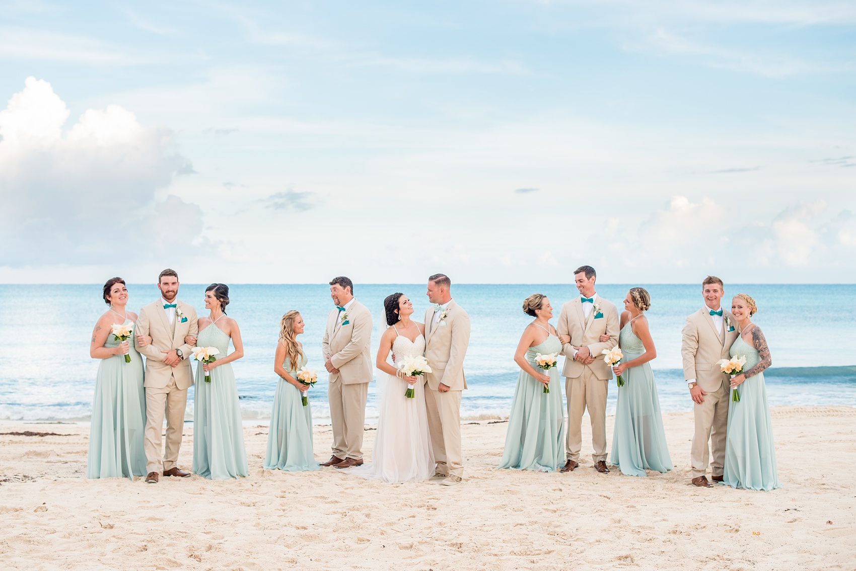 Mikkel Paige Photography photos from a wedding at Grand Paraiso, Mexico, Playa del Carmen Iberostar resort. Picture of the bridal party in mint green gowns and groomsmen in tan suits on the beach.