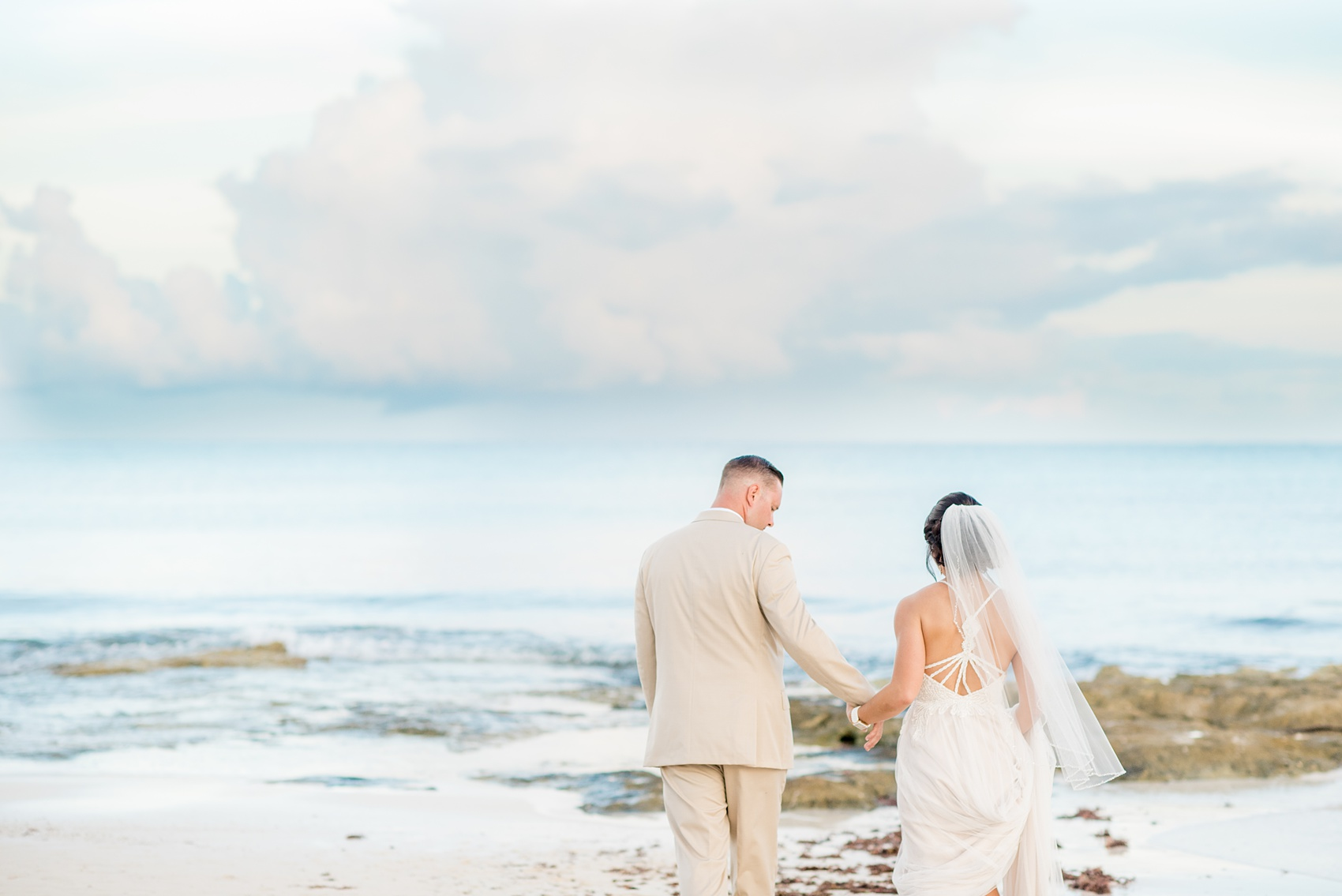 Mikkel Paige Photography photos from a wedding at Grand Paraiso, Mexico, Playa del Carmen Iberostar resort. Picture of the bride and groom walking to on the beach.