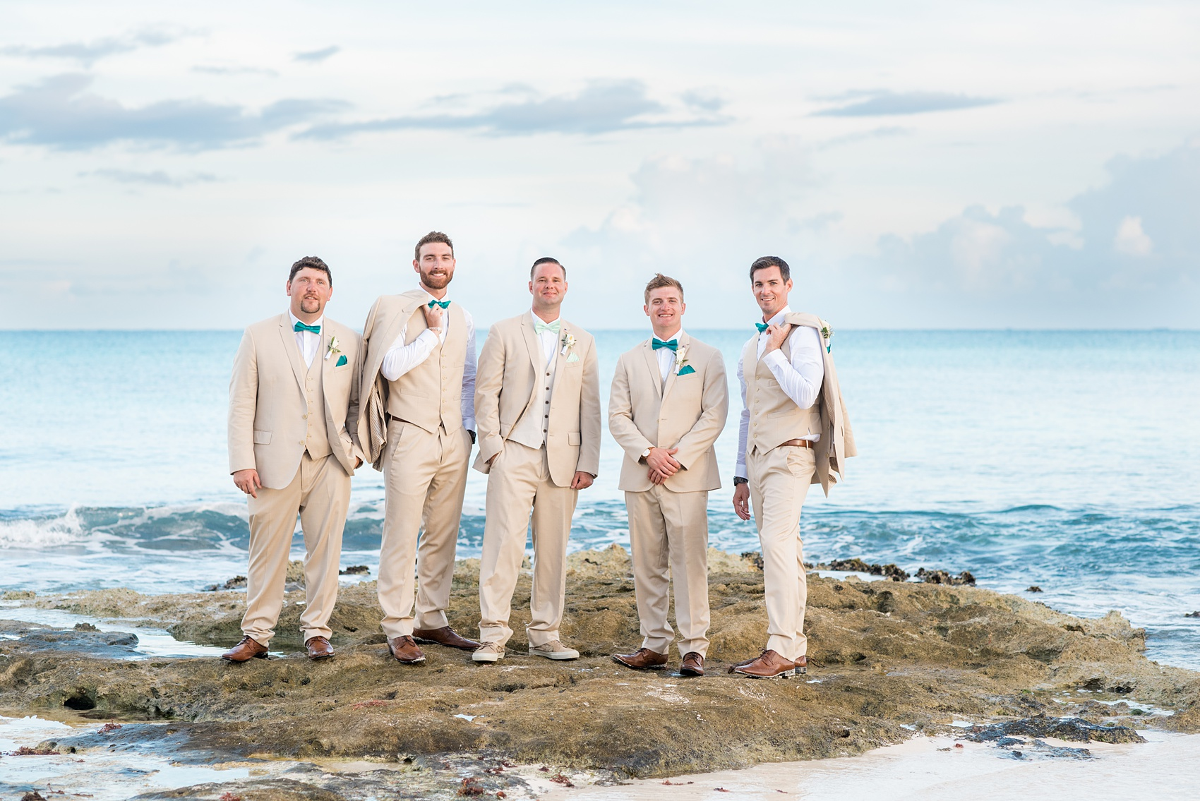 Mikkel Paige Photography photos from a wedding at Grand Paraiso, Mexico, Playa del Carmen Iberostar resort. Picture of the groomsmen on the beach in tan suits and teal bow ties.