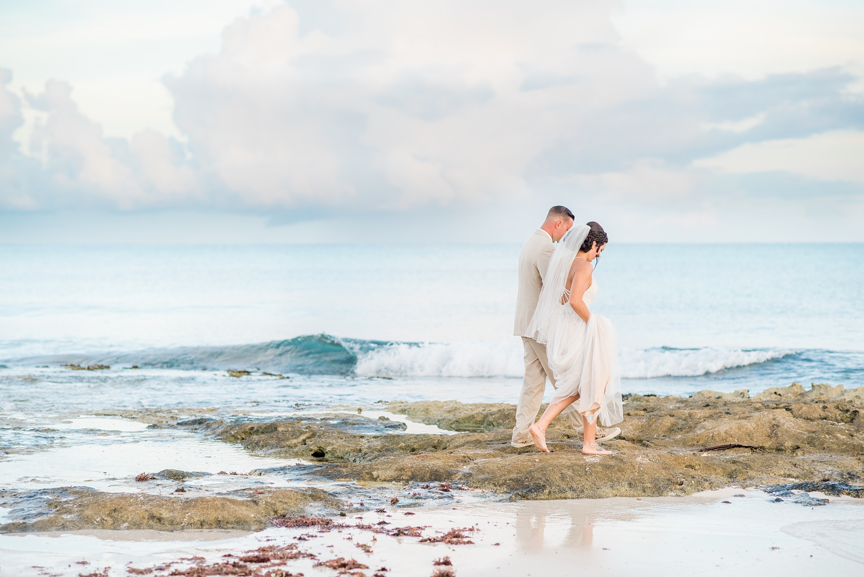 Mikkel Paige Photography photos from a wedding at Grand Paraiso, Mexico, Playa del Carmen Iberostar resort. Picture of the bride and groom walking on the beach.