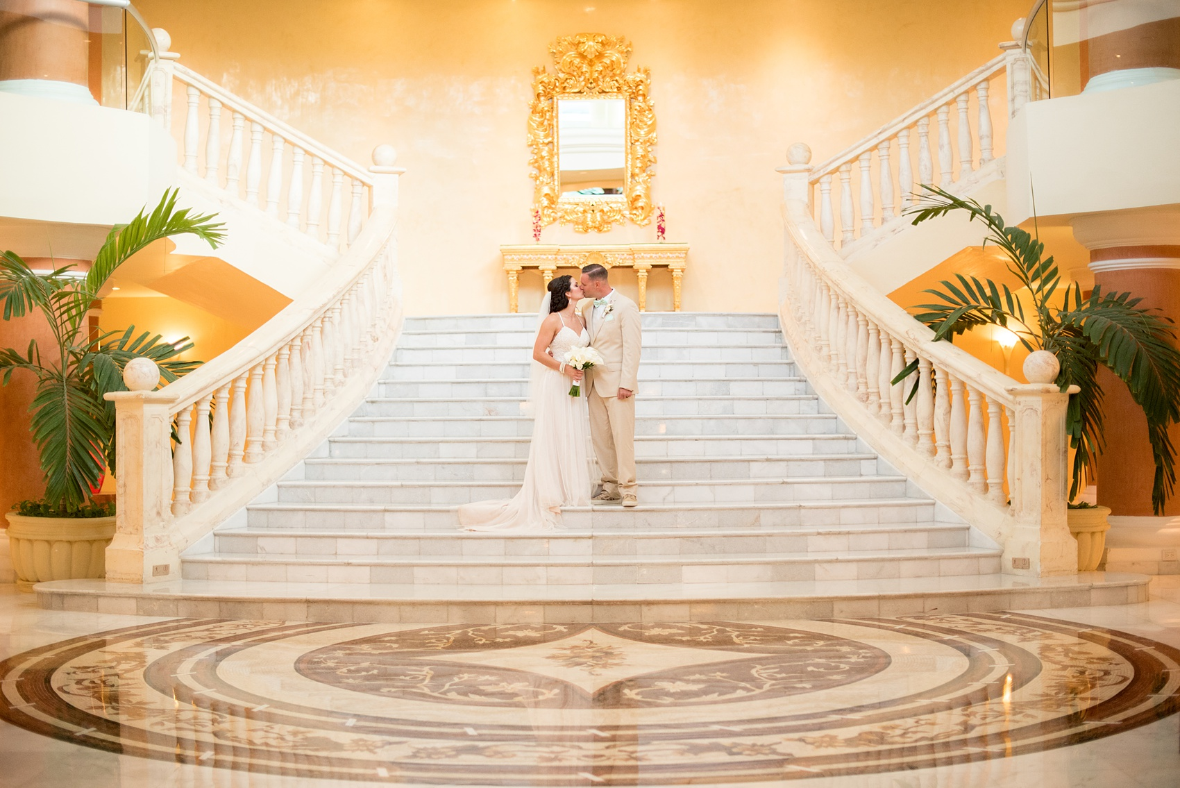 Mikkel Paige Photography photos from a wedding at Grand Paraiso, Mexico, Playa del Carmen Iberostar resort. Picture of the bride and groom kissing on the grand marble staircase in the resort.