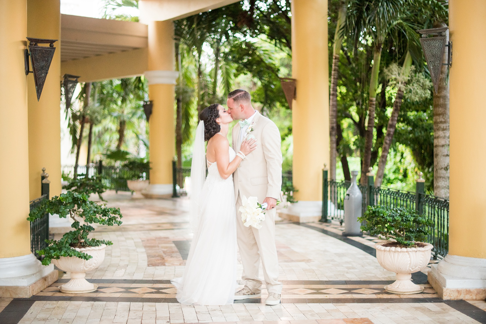 Mikkel Paige Photography photos from a wedding at Grand Paraiso, Mexico, Playa del Carmen Iberostar resort. Picture of the bride and groom kissing in the tropical foliage at the resort.