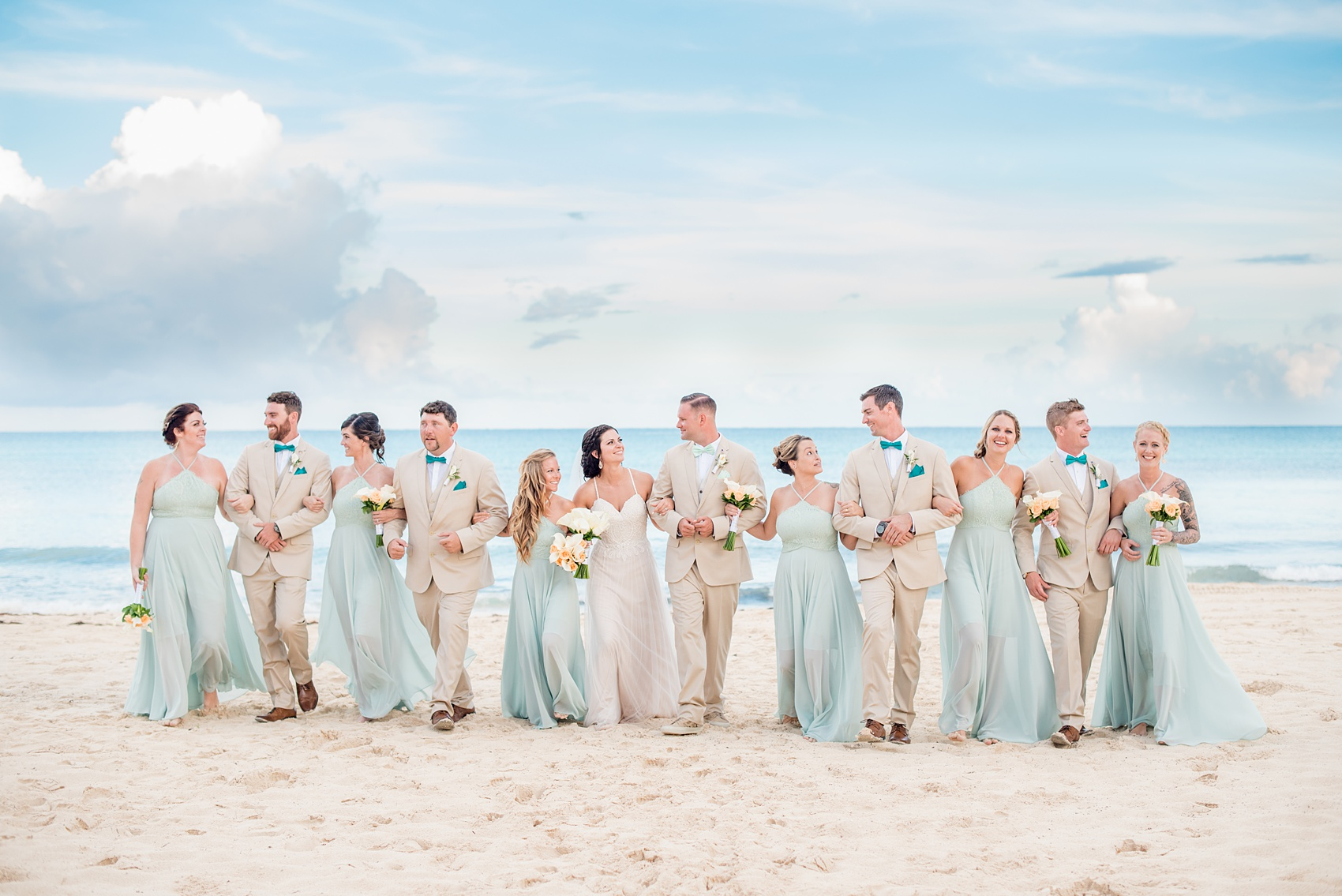 Mikkel Paige Photography photos from a wedding at Grand Paraiso, Mexico, Playa del Carmen Iberostar resort. Picture of the bridal party in mint green gowns and groomsmen in tan suits walking on the beach.