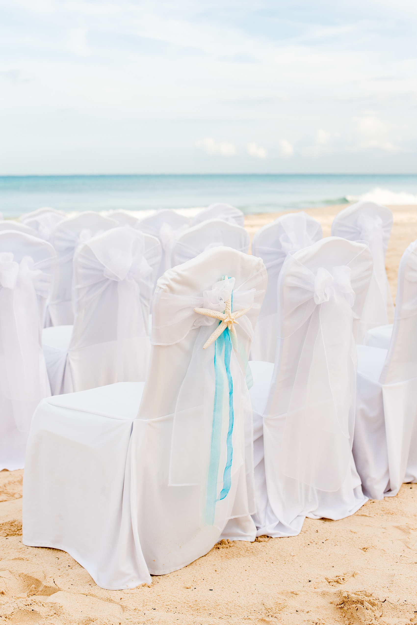 Mikkel Paige Photography photos from a wedding at Grand Paraiso, Mexico, Playa del Carmen Iberostar resort. Picture of the white chairs for the beach ceremony with a starfish and ribbon detail.