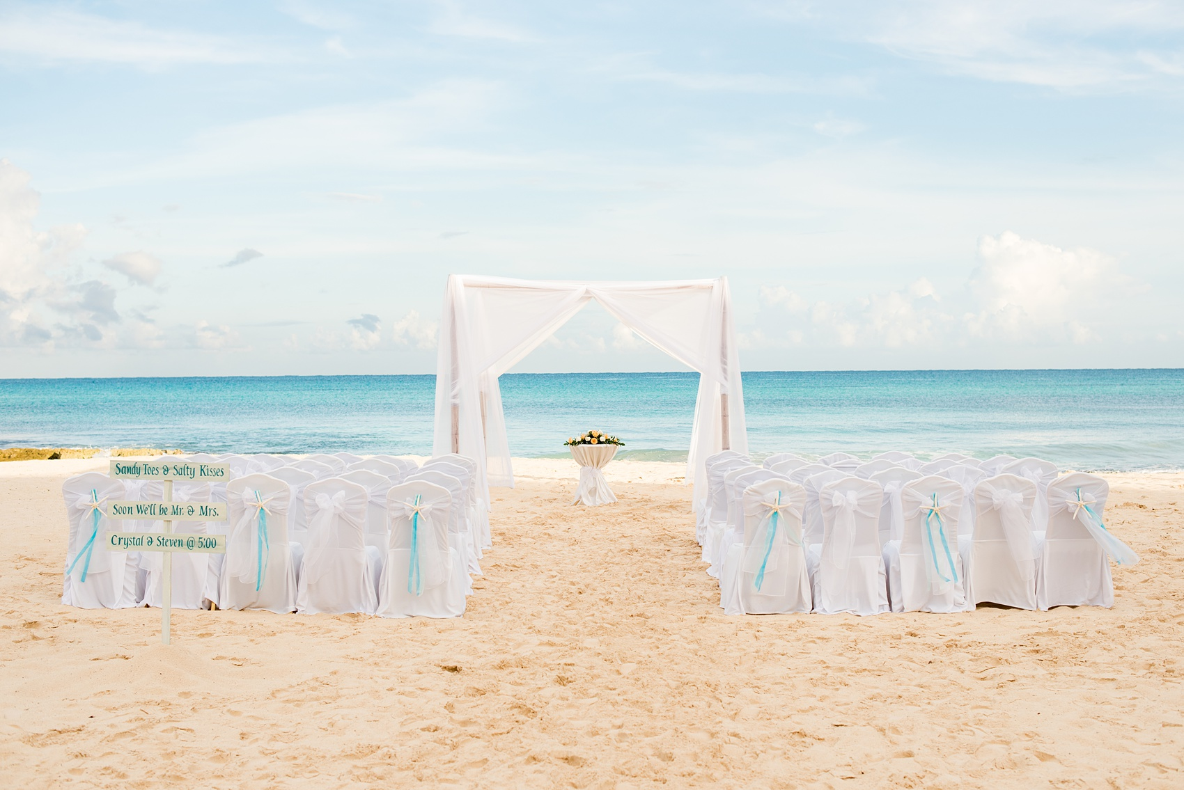 Mikkel Paige Photography photos from a wedding at Grand Paraiso, Mexico, Playa del Carmen Iberostar resort. Picture of the white chairs and fabric arbor for the beach ceremony.