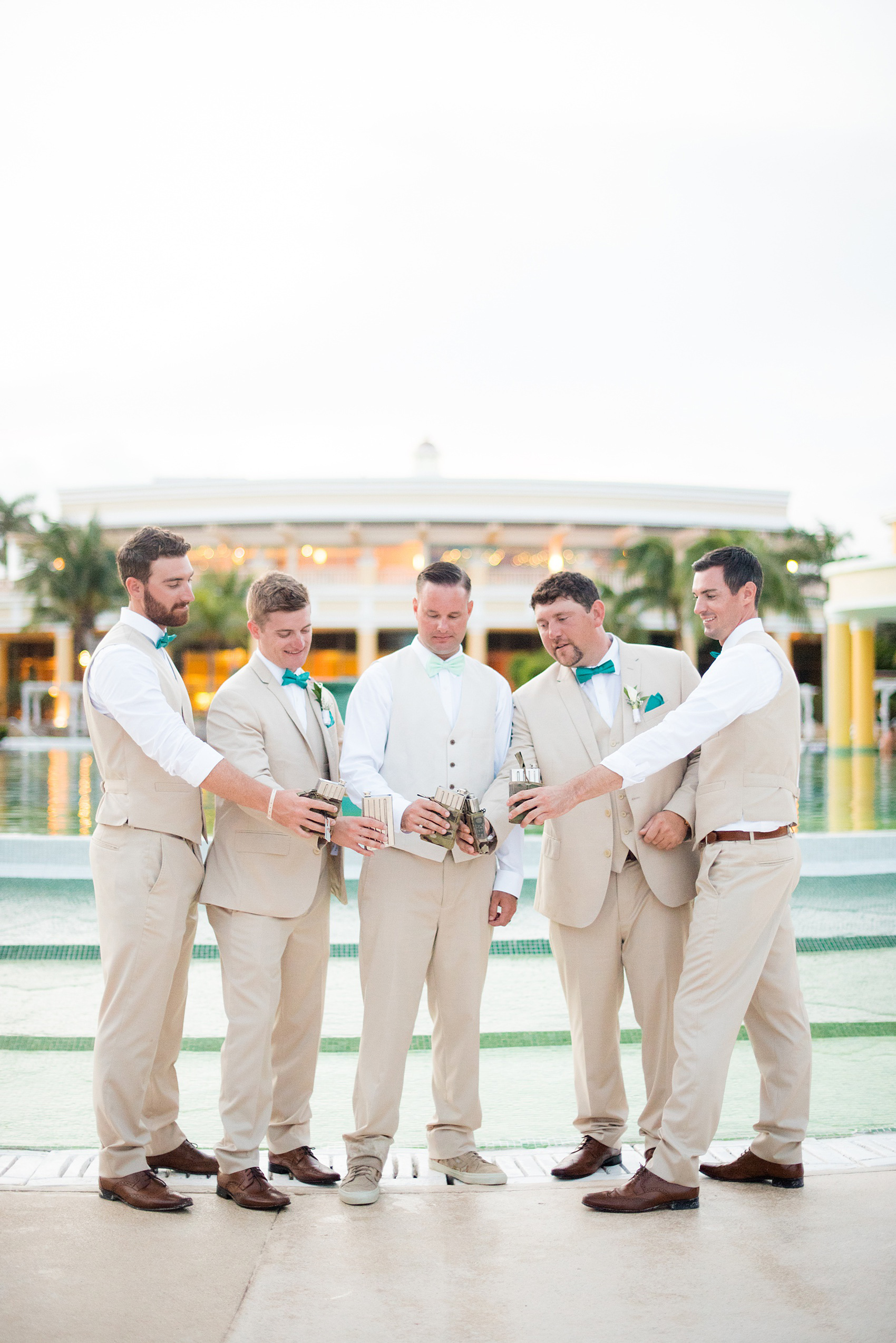Mikkel Paige Photography photos from a wedding at Grand Paraiso, Mexico, Playa del Carmen Iberostar resort. Picture of the groomsmen with their army, military flasks from the groom.