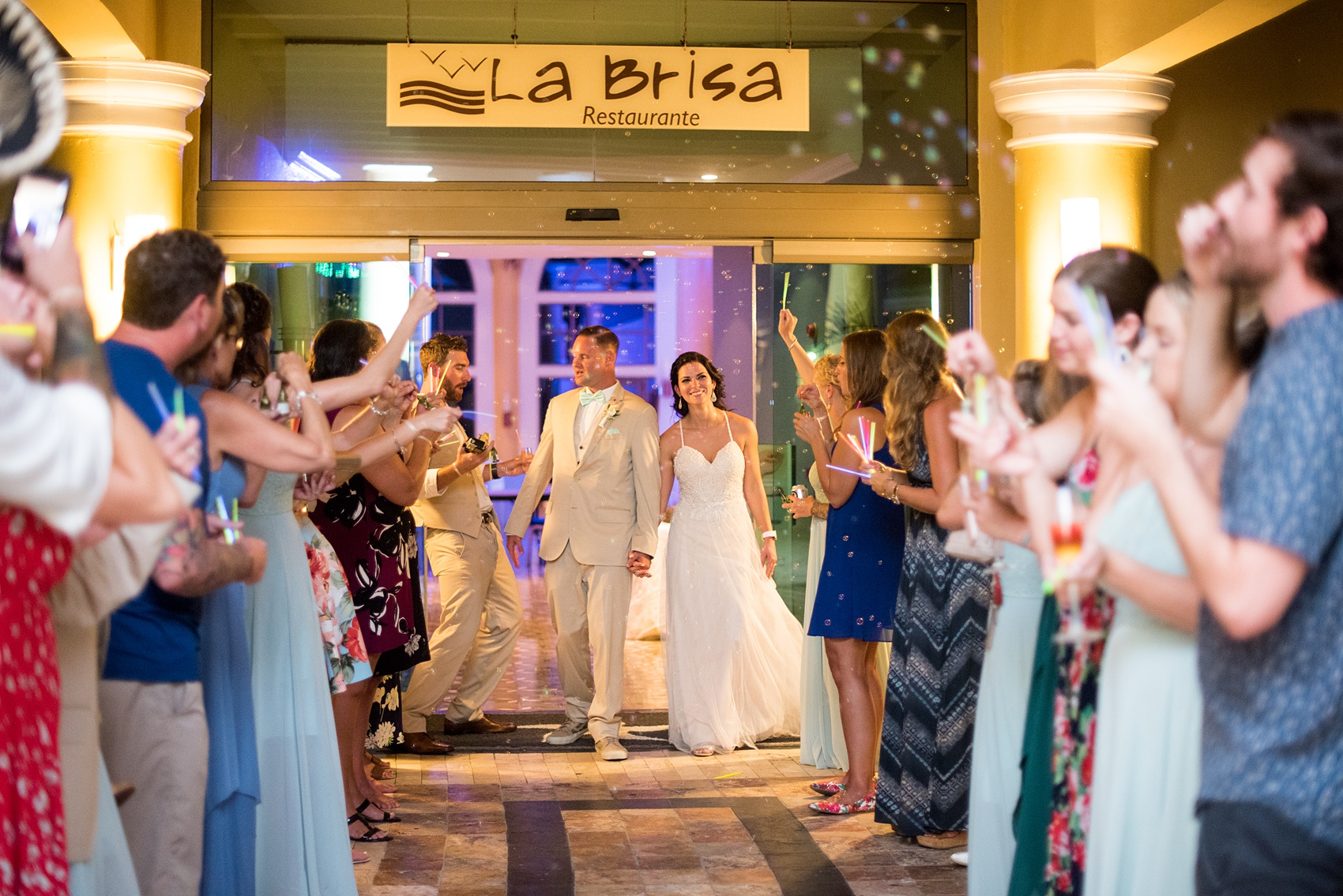 Mikkel Paige Photography photos from a wedding at Grand Paraiso, Mexico, Playa del Carmen Iberostar resort. Picture of bride and groom's bubble and glow stick exit.