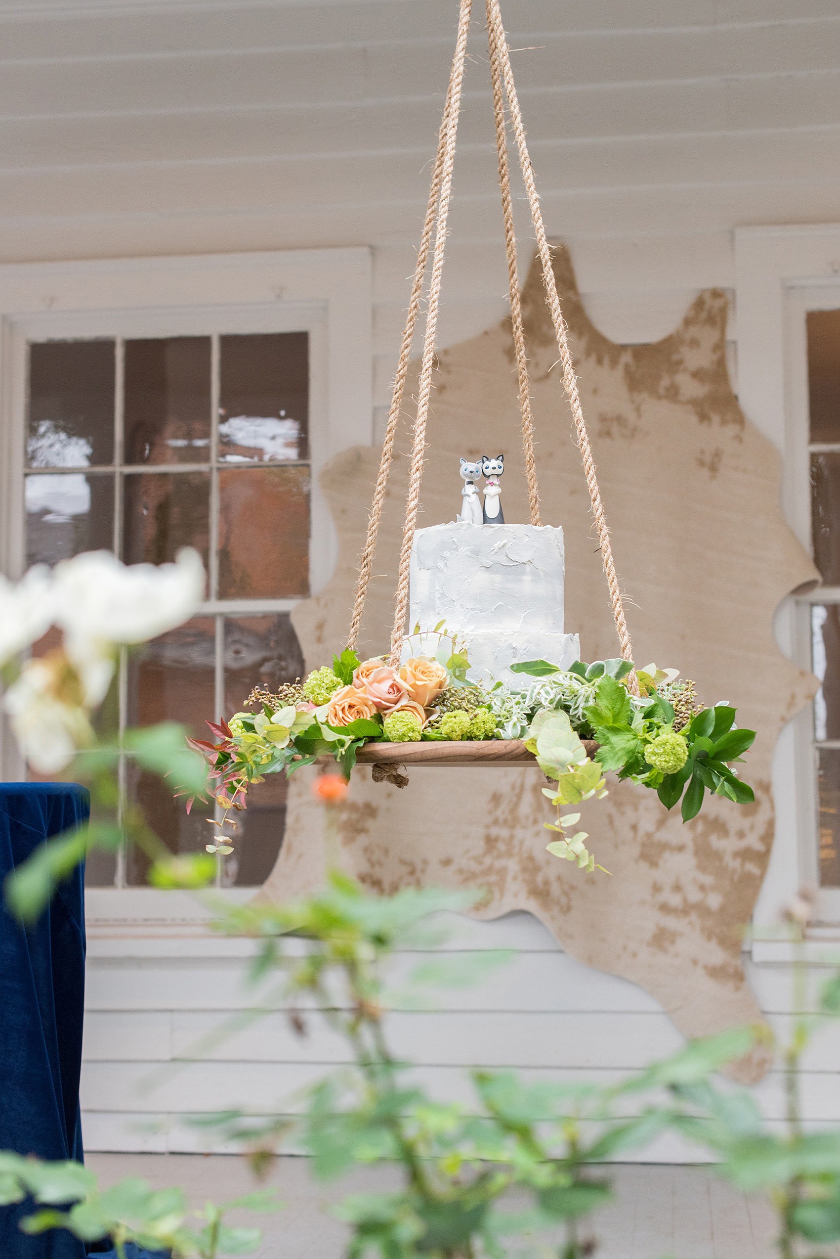 Mikkel Paige Photography photos from a wedding at Leslie-Alford Mims House in North Carolina. Picture of a unique boho cake display: a grey concrete buttercream cake with clay animal cake topper, suspended from the venue on a rope display adorned with flowers.