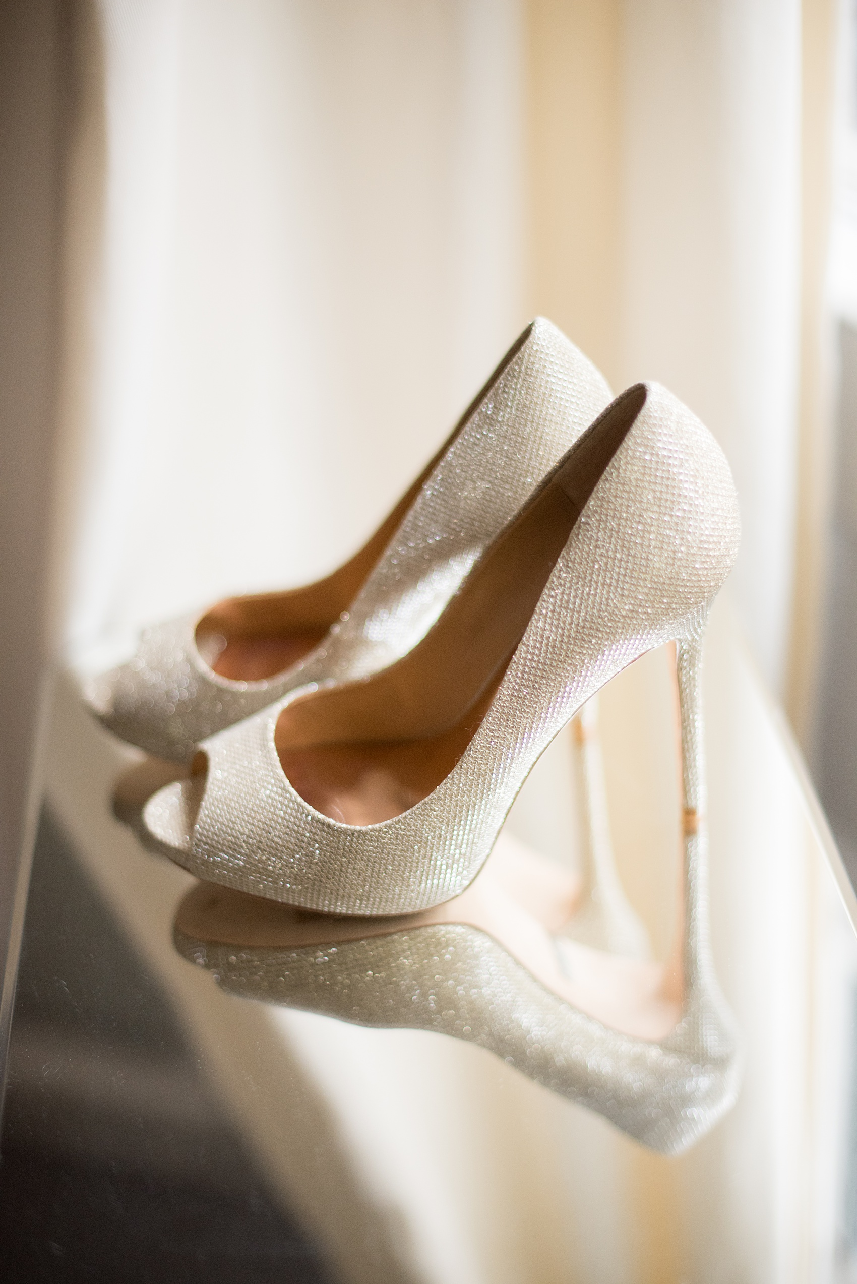 Mikkel Paige Photography photos from a wedding at Leslie-Alford Mims House in North Carolina. Picture of the bride's metallic gold Badgley Mischka heels.