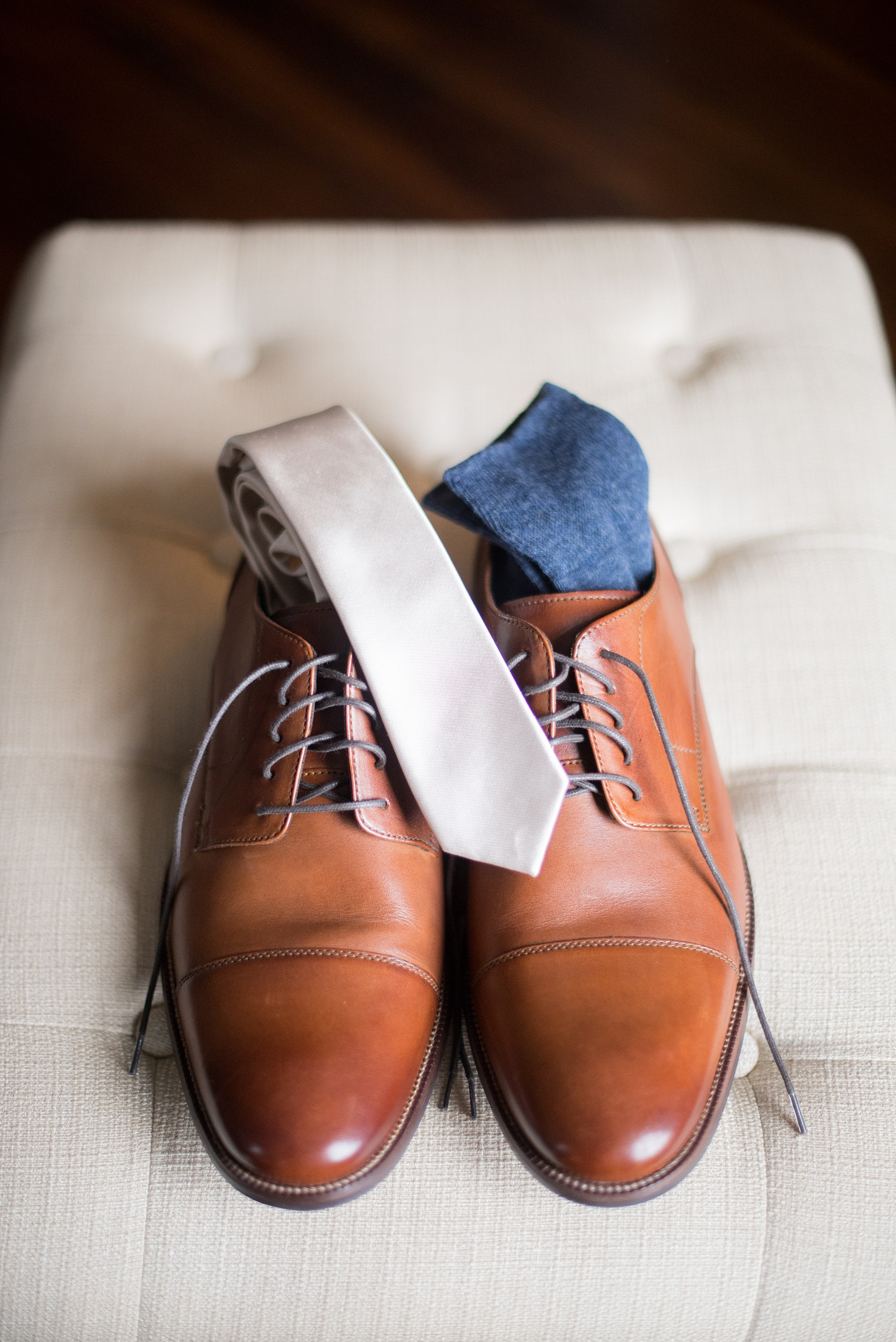 Mikkel Paige Photography photos from a wedding at Leslie-Alford Mims House in North Carolina. Picture of the groom's brown leather shoes, navy socks and off white tie.