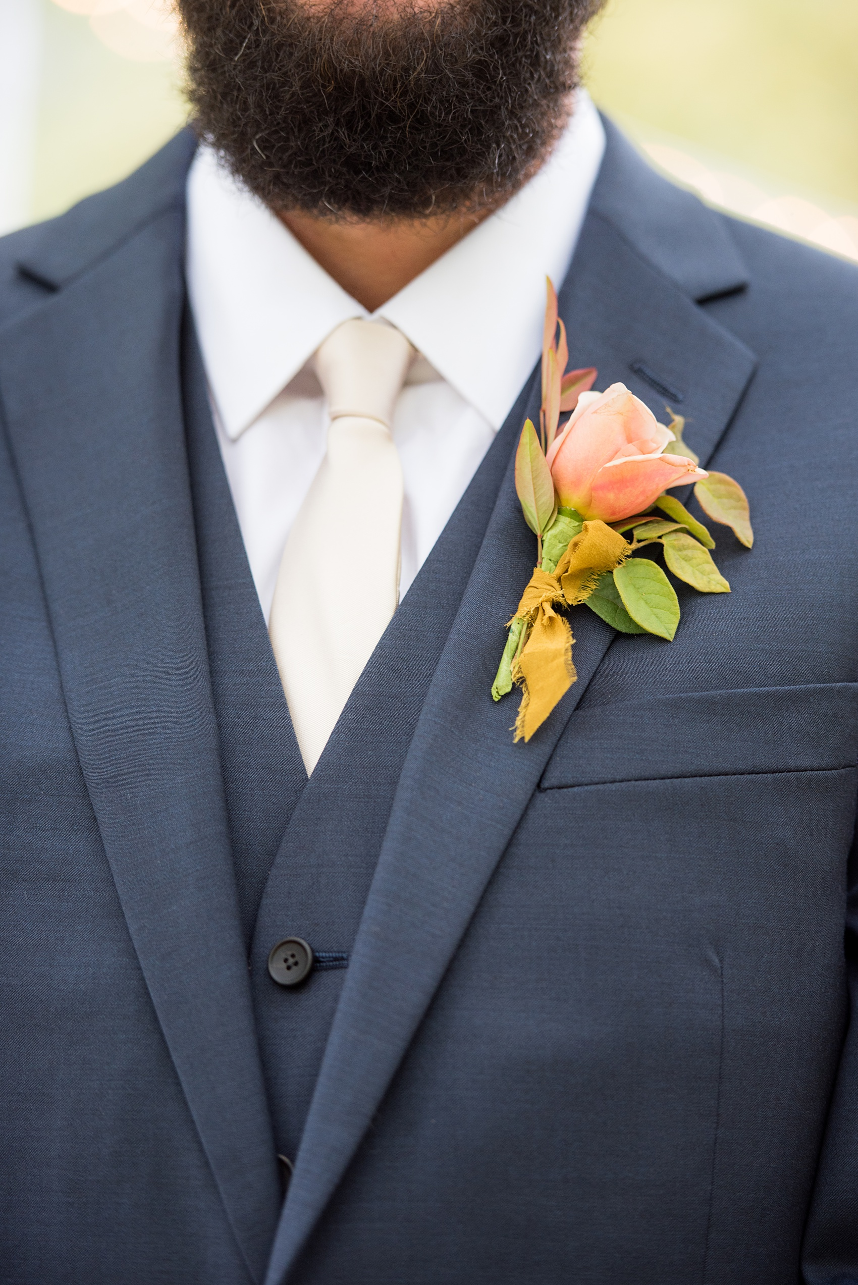 Mikkel Paige Photography photos from a wedding at Leslie-Alford Mims House in North Carolina. Detail picture of the groom's double breasted navy linen suit and fall boutonniere.