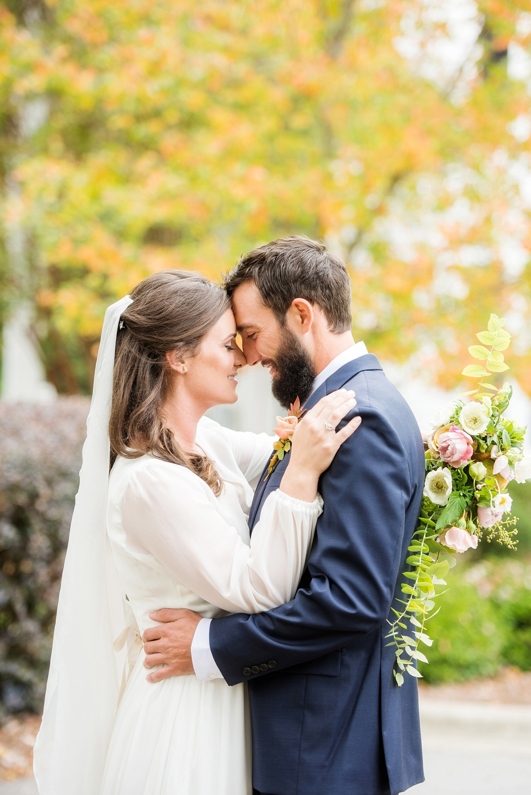Mikkel Paige Photography photos from a wedding at Leslie-Alford Mims House in North Carolina. Picture of the Boho bride and groom in a navy suit for their Mad Dash Wedding, complete with colorful fall foliage.