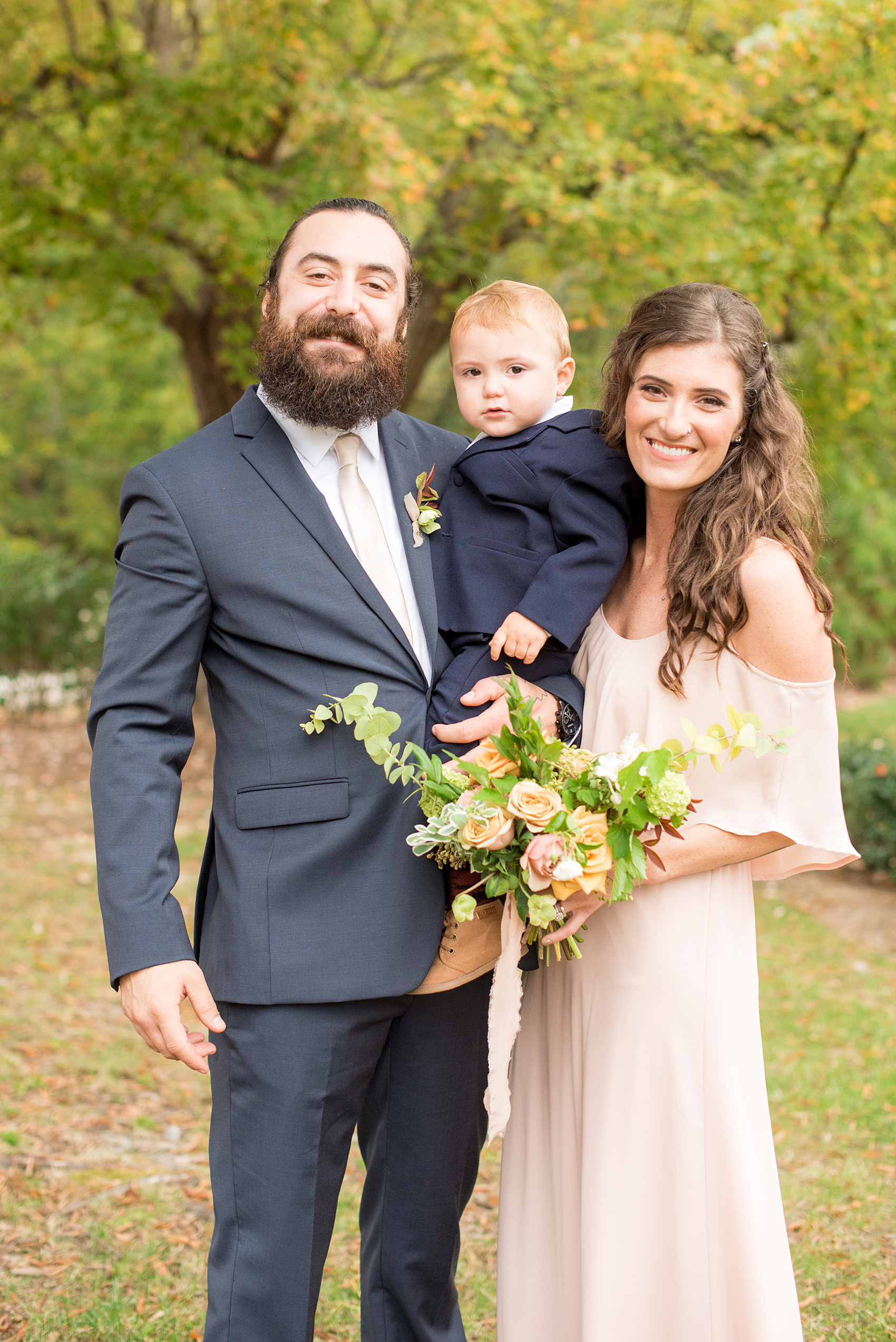 Mikkel Paige Photography photos from a wedding at Leslie-Alford Mims House in North Carolina. Picture of a groomsmen and bridesmaids, with their ring bearer toddler son, in navy linen suits and light pink gown.