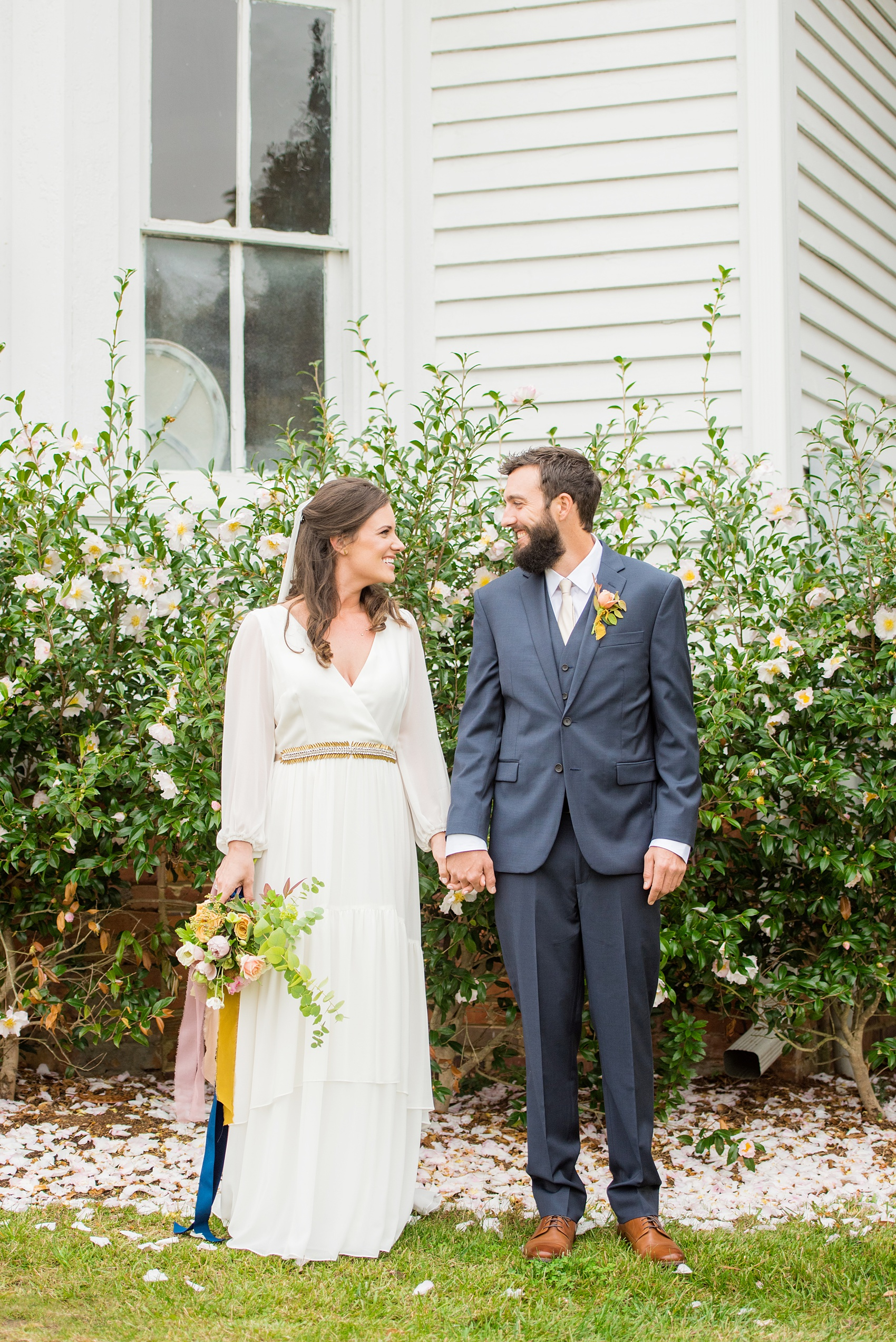 Mikkel Paige Photography photos from a wedding at Leslie-Alford Mims House in North Carolina. Picture of the bride and groom at the historic southern home venue amidst Camellia pink flower petals.