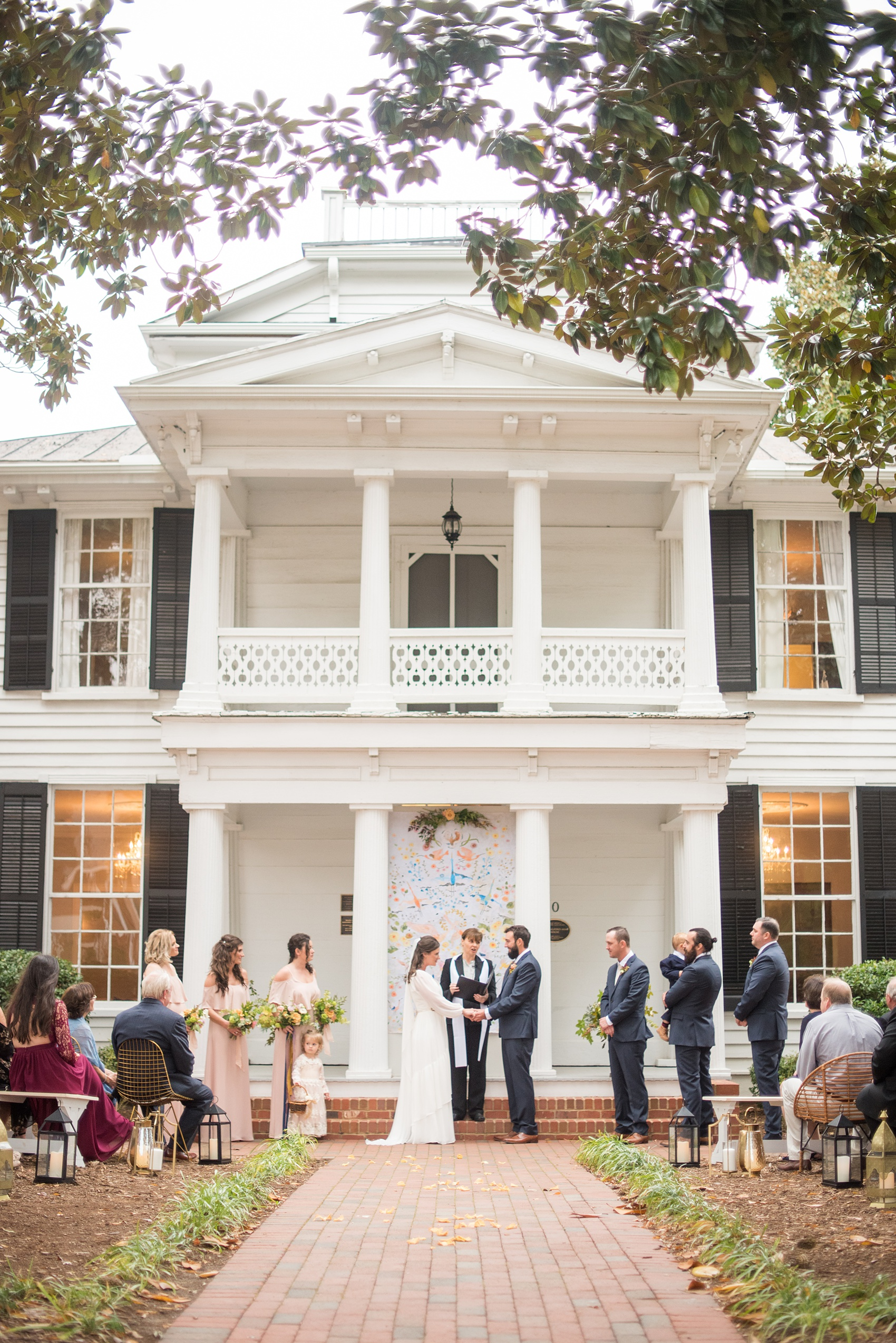 Mikkel Paige Photography photos from a wedding at Leslie-Alford Mims House in North Carolina. Picture of the outdoor ceremony with colorful BHLDN batik backdrop for nuptials at the historic southern home.
