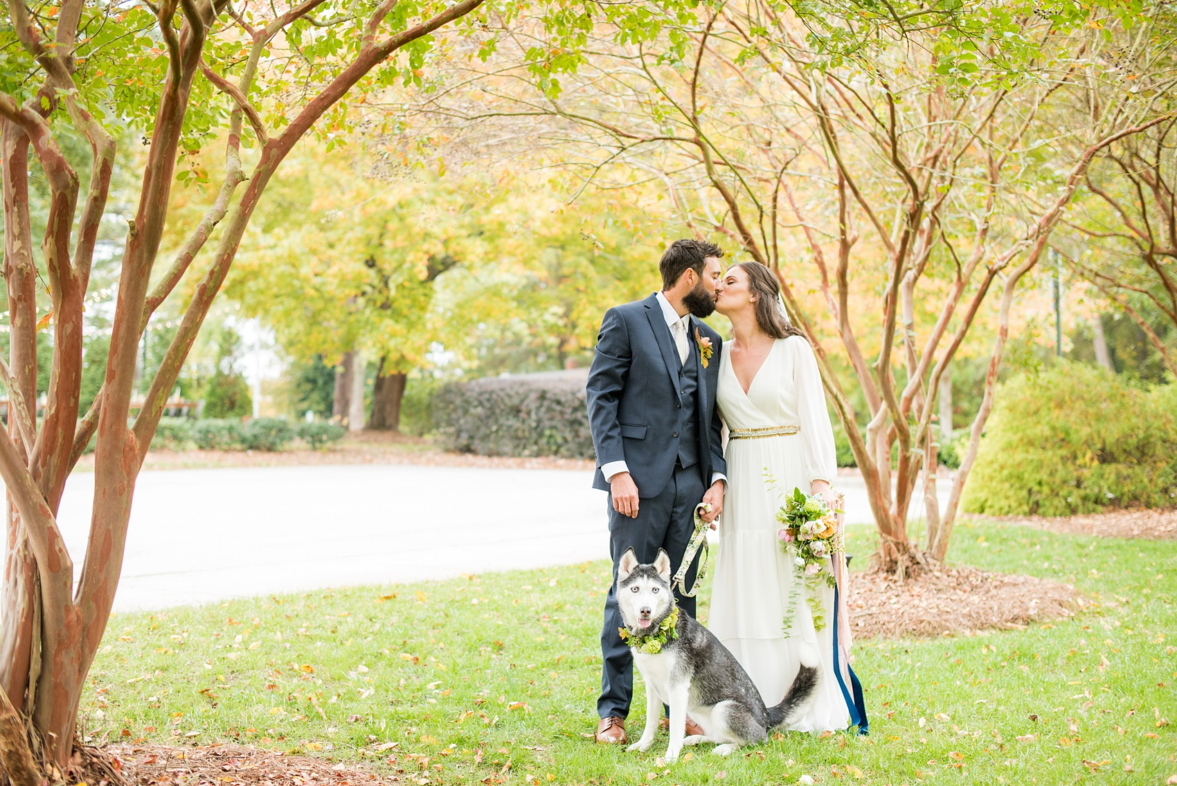 Mikkel Paige Photography photos from a wedding at Leslie-Alford Mims House in North Carolina. Picture of the Boho bride and groom with their Husky dog in a floral collar on their fall Mad Dash Weddings event day.