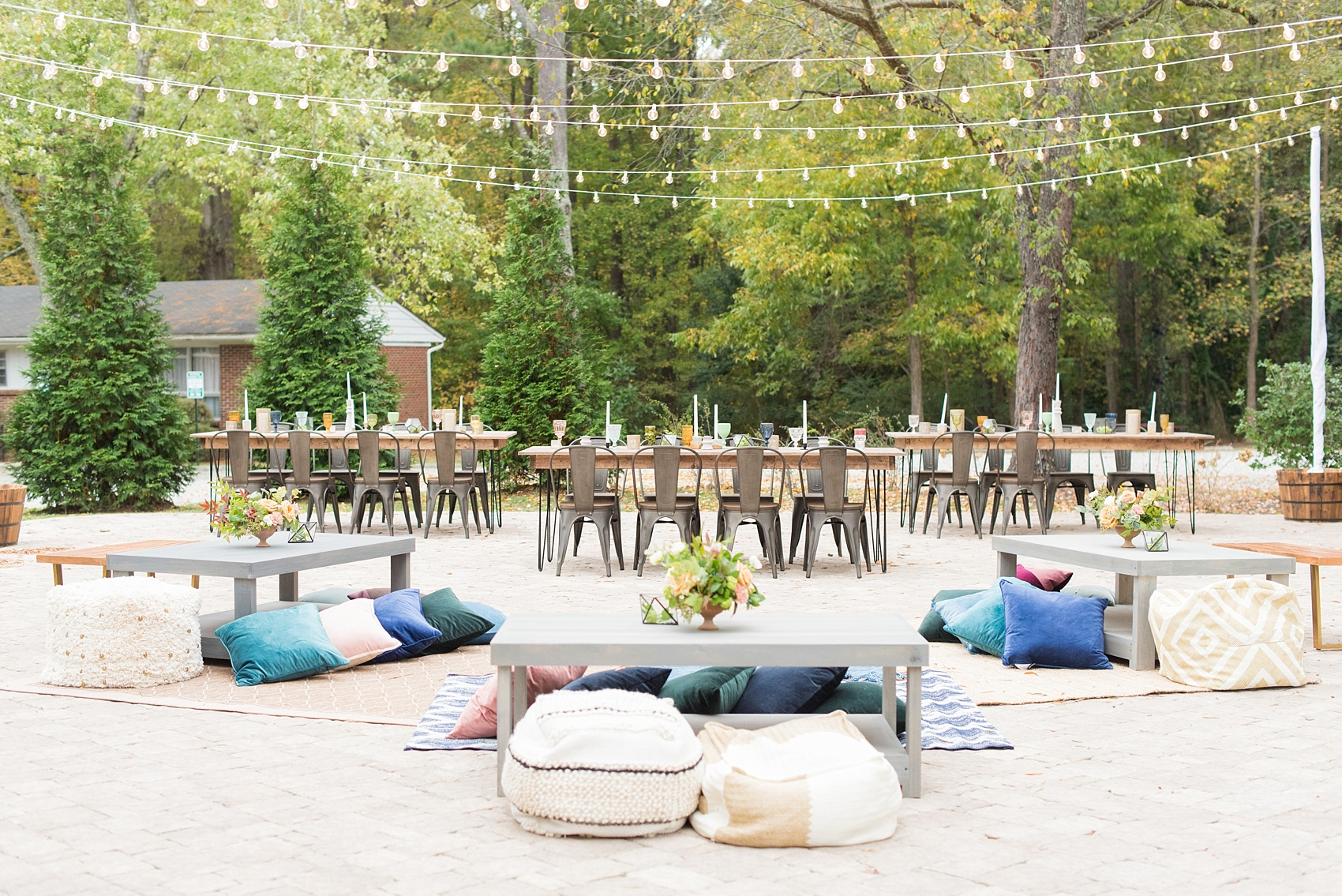 Mikkel Paige Photography photos from a wedding at Leslie-Alford Mims House in North Carolina. Picture of the outdoor reception setup with farm tables, metal chairs, rugs and pillow seating and market lights.