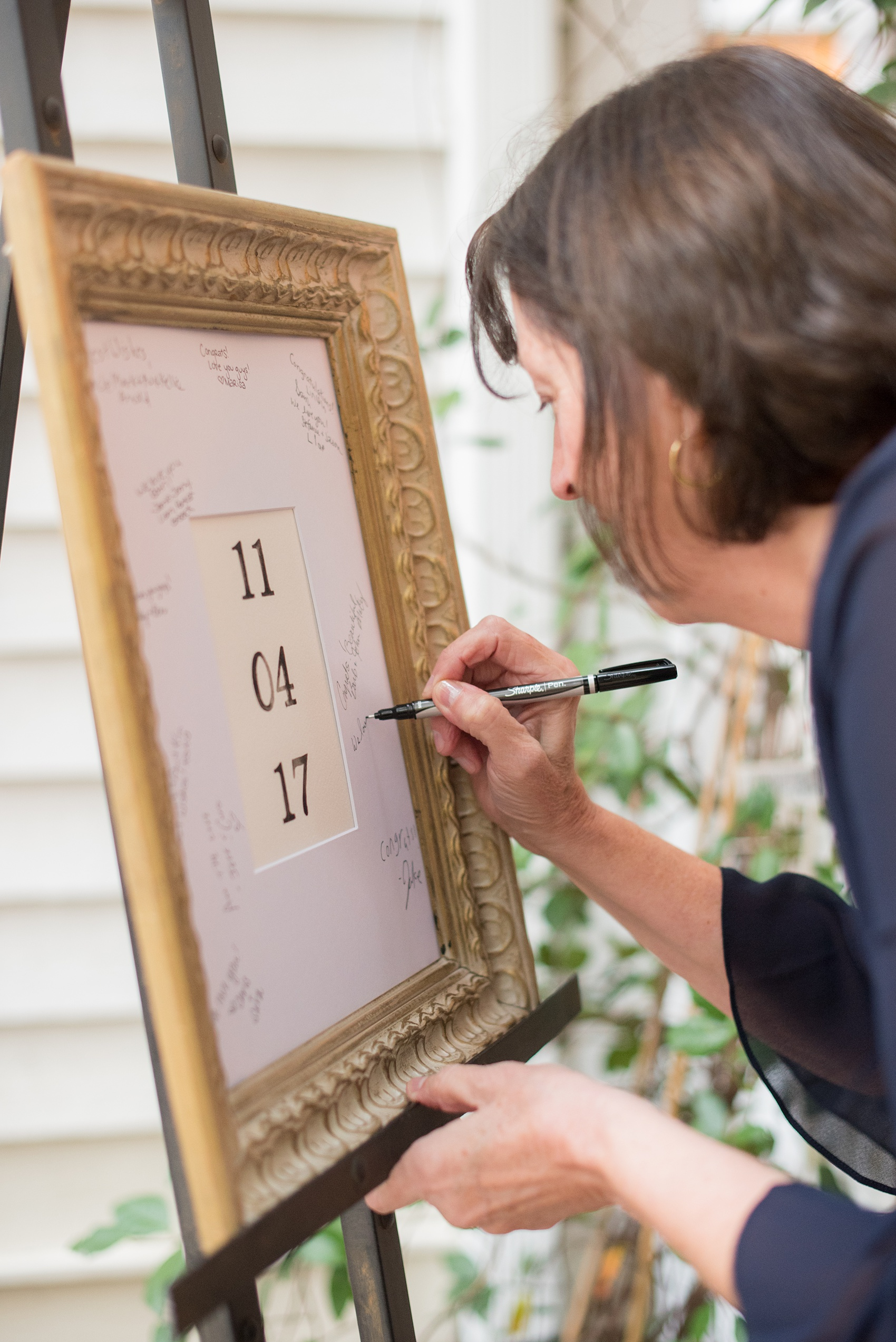 Mikkel Paige Photography photos from Leslie-Alford Mims House in North Carolina. Picture of a guest signing their wedding date frame board.