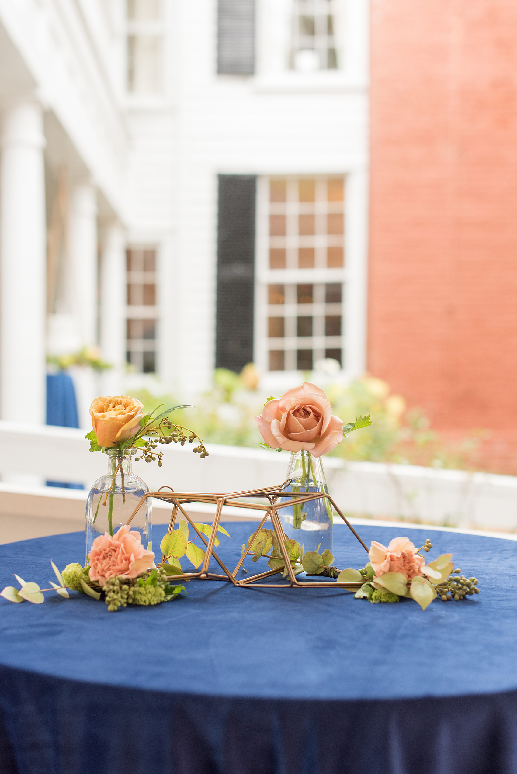 Mikkel Paige Photography photos from a wedding at Leslie-Alford Mims House in North Carolina. Picture of a blue velvet cocktail table with gold metal geometric shapes and colorful fall flowers.