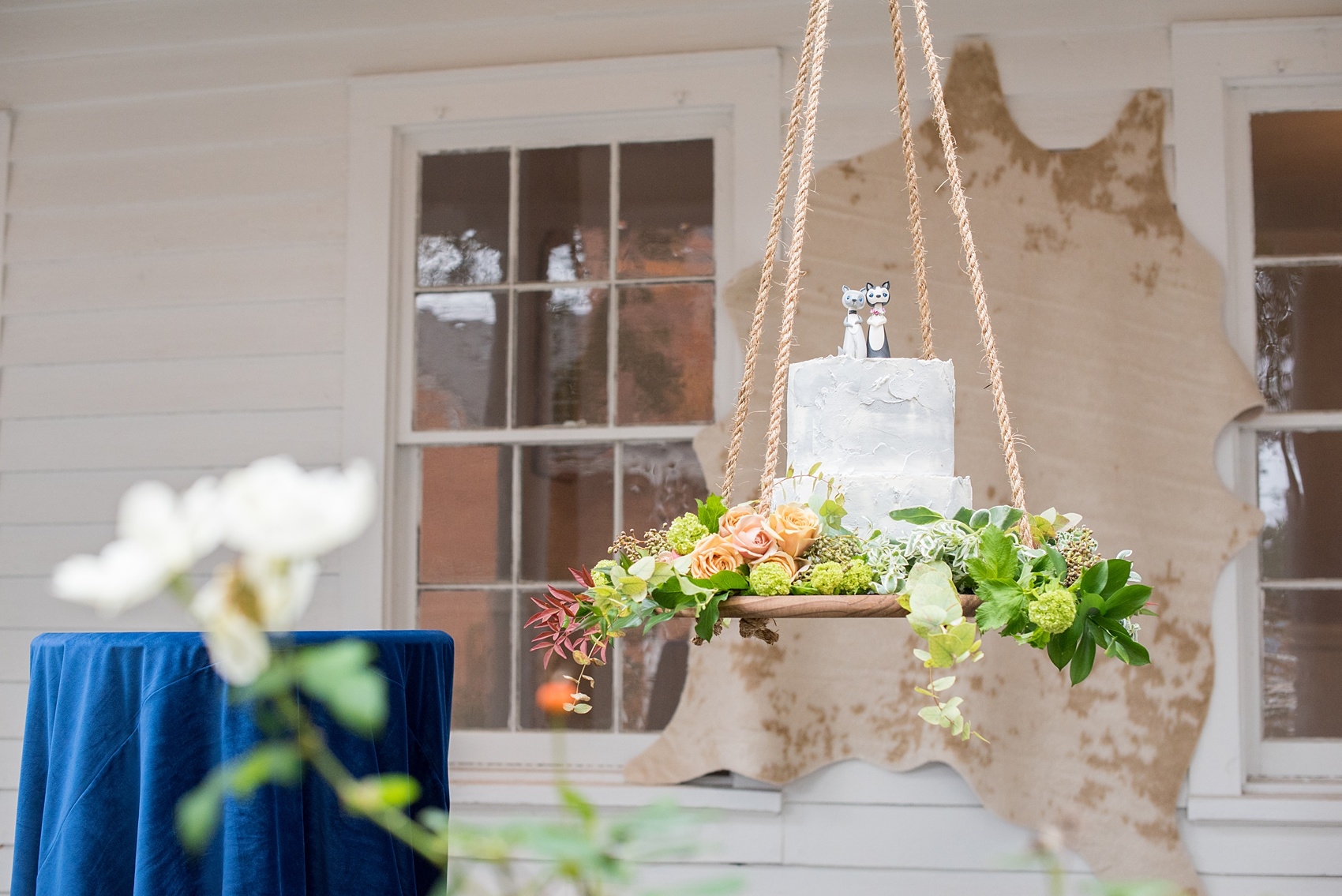 Mikkel Paige Photography photos from a wedding at Leslie-Alford Mims House in North Carolina. Picture of the concrete cake with clay animal cake topper, suspended from the venue on a rope display adorned with flowers.